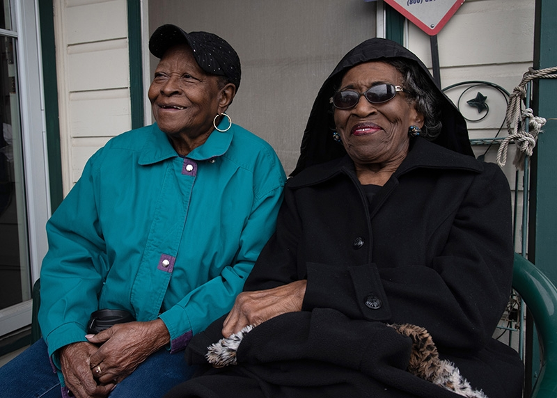 Grace Jones (left) and Marceline Gipson watch San Antonio's MLK March from their porch on Monday. Gipson said they welcome marchers to visit them to grab a cup of coffee or hugs. Photo by V. Finster | Heron Contributor
