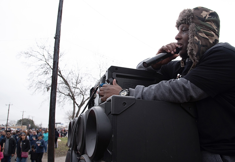 "Joseph Clay encourages marchers over a sound system in front of his house during the annual MLK March. Clay said he has done this the past 17 years because ""Today is a happy day."" Photo by V. Finster 