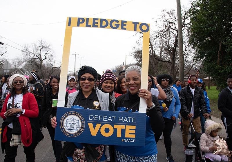 Zelma Shannon (from left), Cynthia Gibbs and Darlene Jones, members of the NAACP San Antonio chapter hold their sign during the annual MLK March Monday. Photo by V. Finster | Heron Contributor