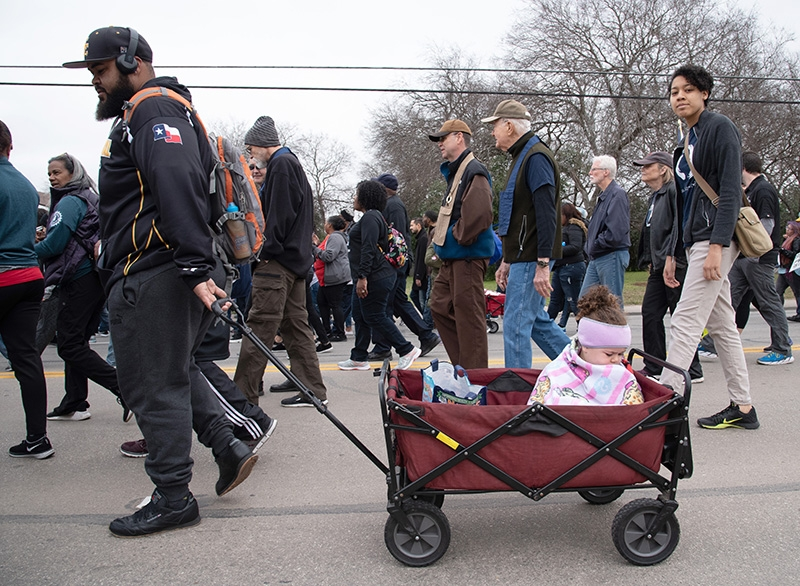 "Brett Robinson pulls a wagon carrying daughter Emma Robinson, 4, during the annual MLK March Monday. Robinson, who has attended the march for over 30 years, said he marches because Dr. King's message ""Is a dream we all should believe in."" Photo by V. Finster 