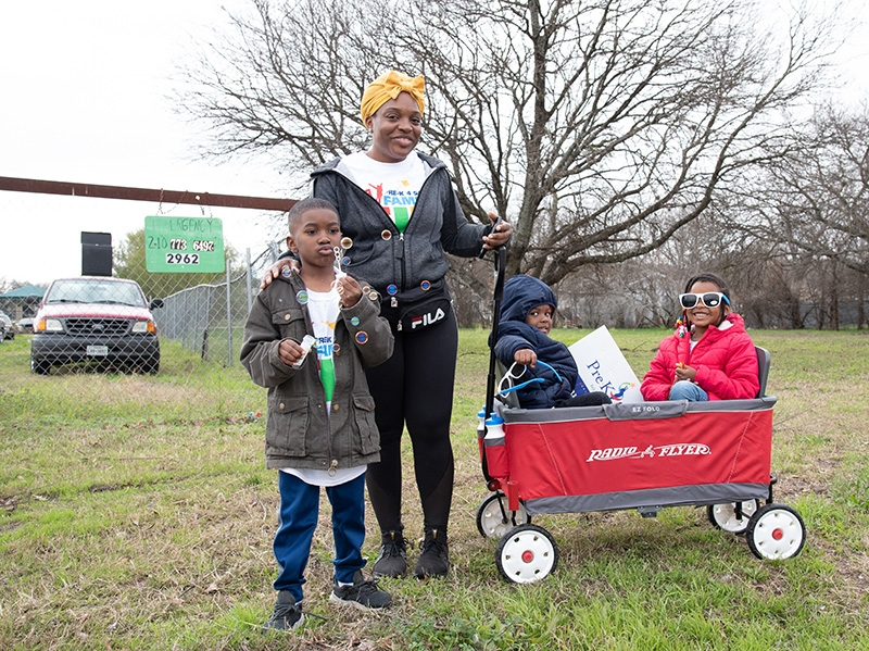 Sheldrick Griner stands with her children Corey, 5, Cameron, 3, and Charity Griner during the annual MLK March Monday. New residents of San Antonio, Griner said she was excited to finally be able to watch the march. Photo by V. Finster | Heron Contributor