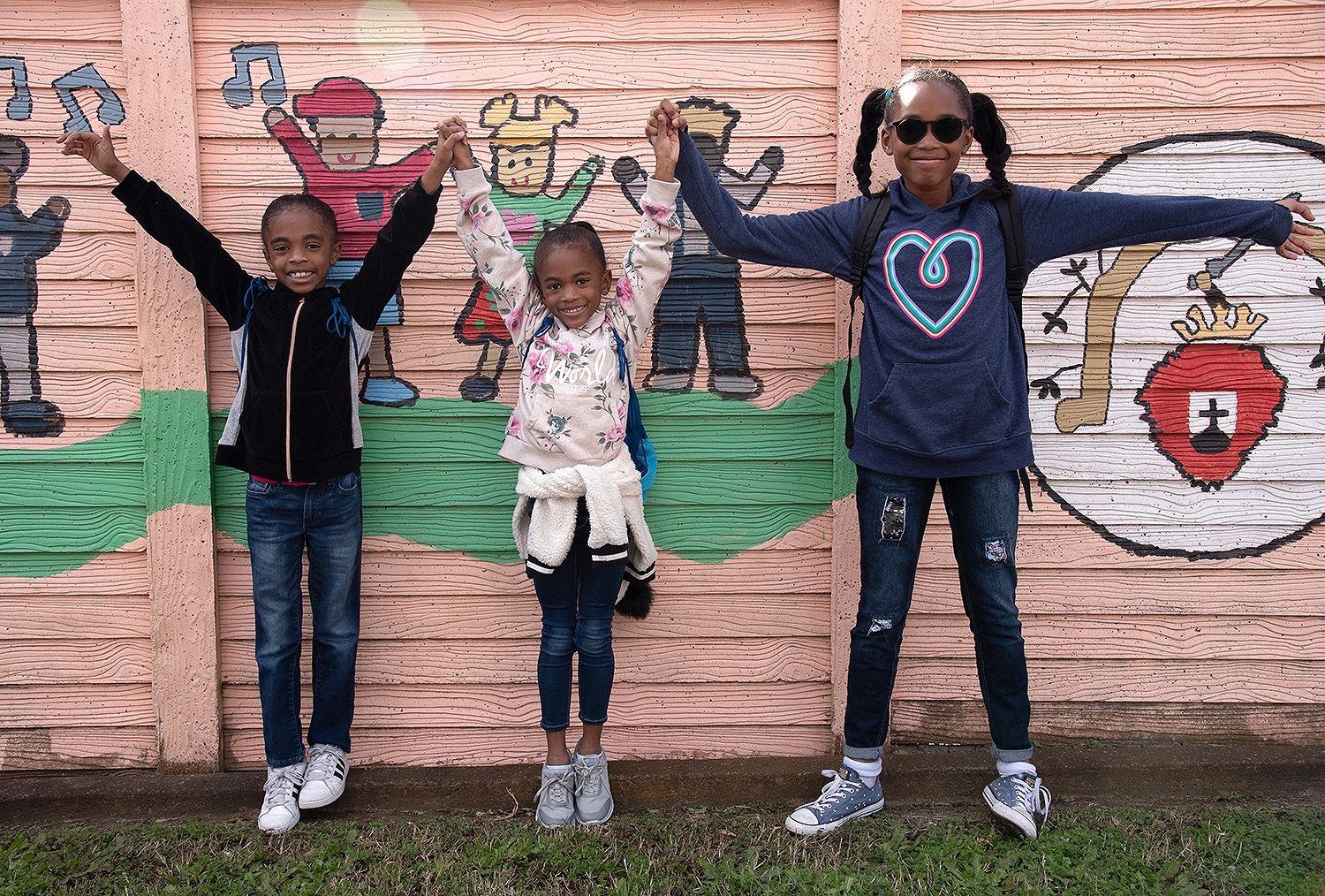 Macy (from left), Abigail and Taylor pose for a photo during the annual MLK March Monday. Photo by V. Finster | Heron Contributor