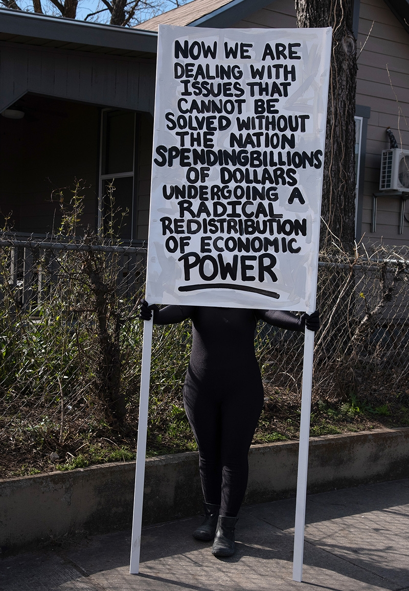 Performance artist Scartheia holds a sign during the annual MLK March Monday. Photo by V. Finster | Heron Contributor