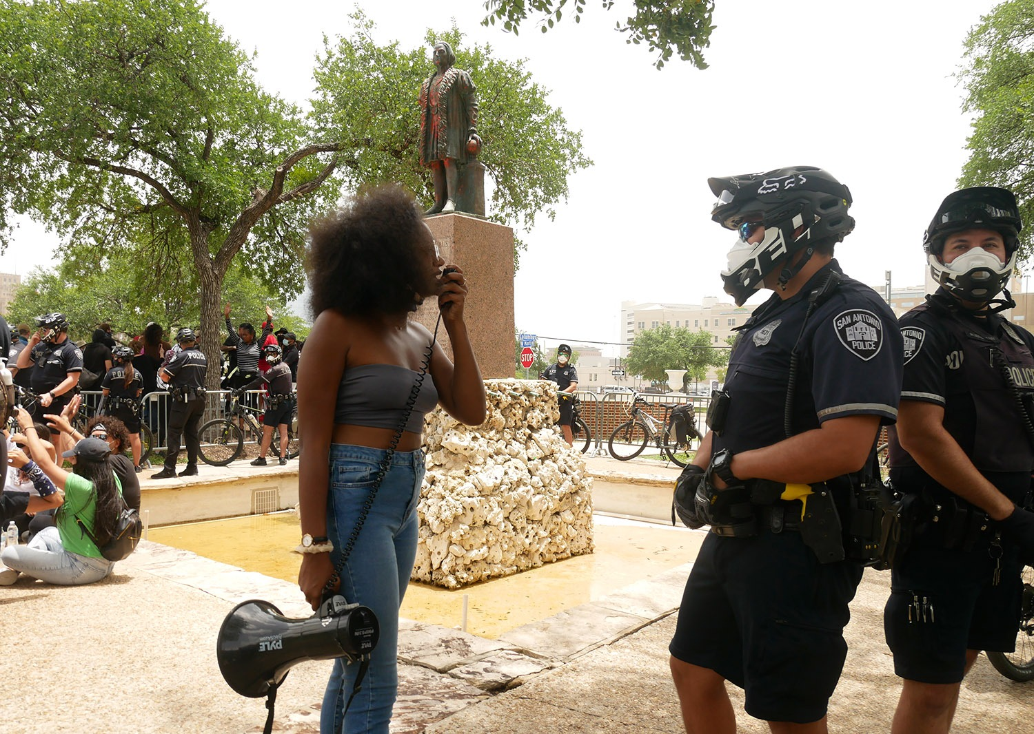 Kimiya Factory, 21, an organizer for the local Black Lives Matter movement, confronts police officers during a protest for the removal of the Columbus statue Saturday, June 27, 2020, at Columbus Park, 200 Columbus St. Photo by Michelle Delrey | Heron contributor