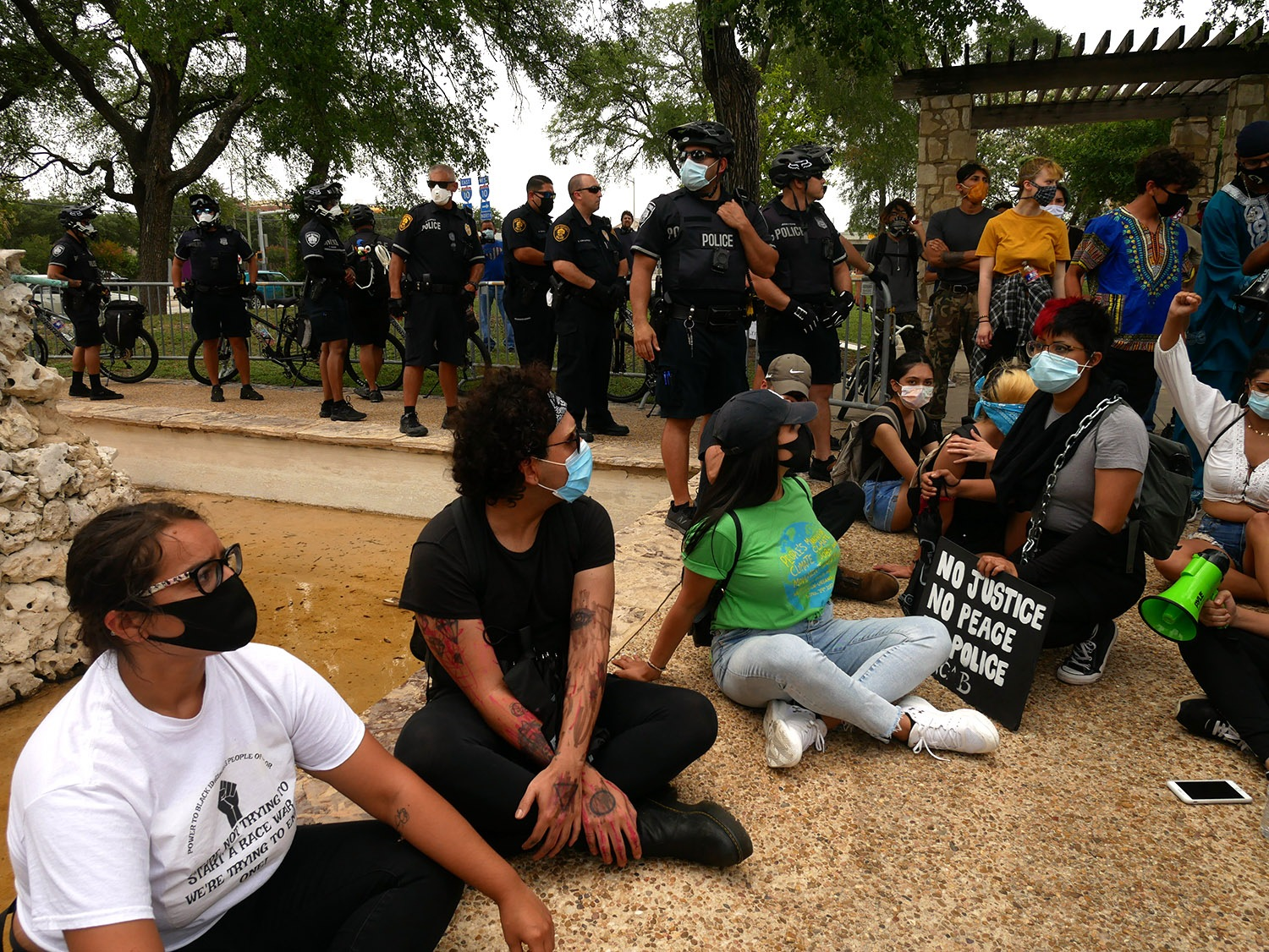 Advocates for the removal of the Christopher Columbus statue downtown sit around the statue as police officers stand by on Saturday, June 27, 2020, at Columbus Park. <b><em>Photo by Michelle Delrey | Heron contributor</em></b>