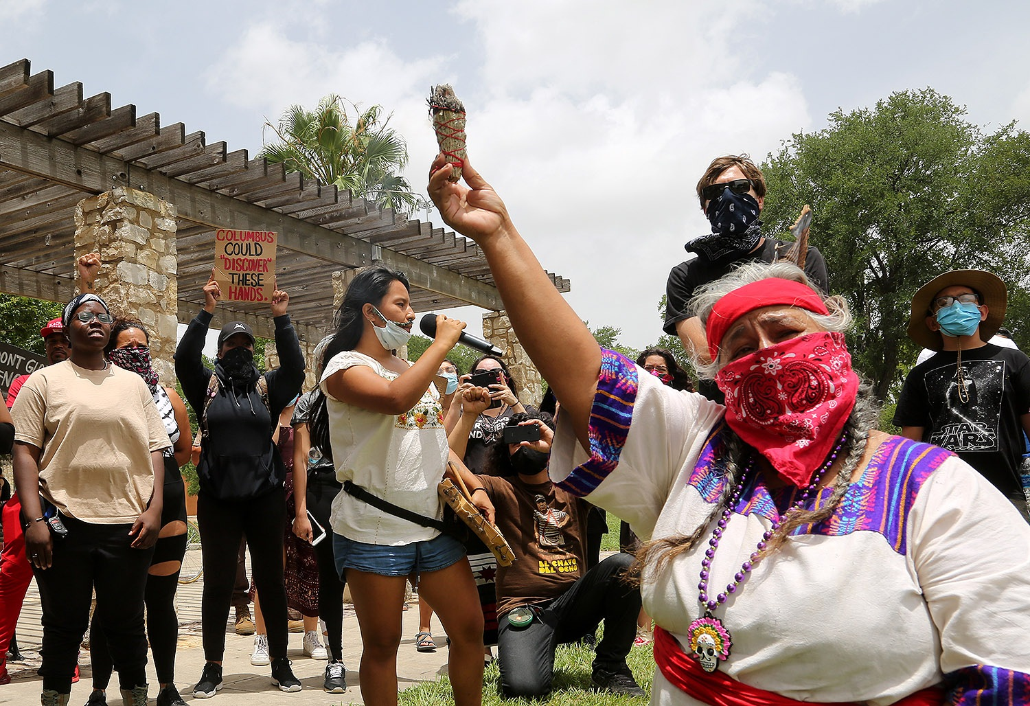 Ceiba (center) speaks to a group of roughly 50 advocates for the removal of the Christopher Columbus statue as Diana Uriegas (right) offers a sage cleanse during a protest Saturday, June 27, 2020, at Columbus Park. <b><em>Photo by Ben Olivo | Heron</em></b>