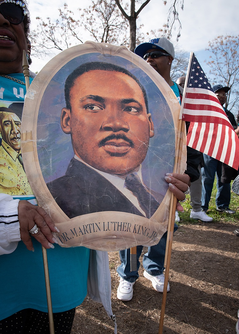 Robbie Thompson, 74, holds a poster before the start of the Martin Luther King, Jr. March on Jan. 20, 2020. Thompson has attended every march, which was in its 33rd year as a City of San Antonio event. <b><em>Photo by V. Finster | Heron contributor</em></b>