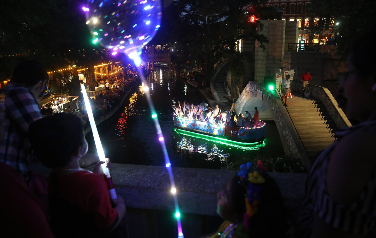 The Texas Cavaliers River Parade was back Monday night, June 21, after being canceled last year due to Covid-19. In this photo, the Gallegos family watches the parade from the Market Street bridge. <em>Photo by Ben Olivo   Heron</em>