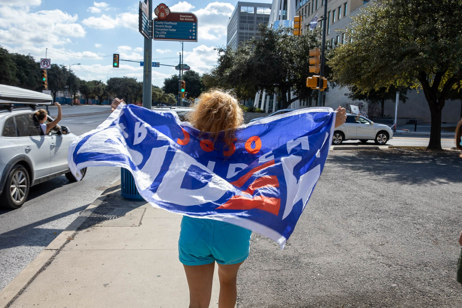 Jasmine Calvo, 17 walks with a President Biden flag along side the caravan celebrating the President-elect Joe Biden and Kamala Harris's win on November 7, 2020. Photo by Stephanie Marquez | Heron contributor