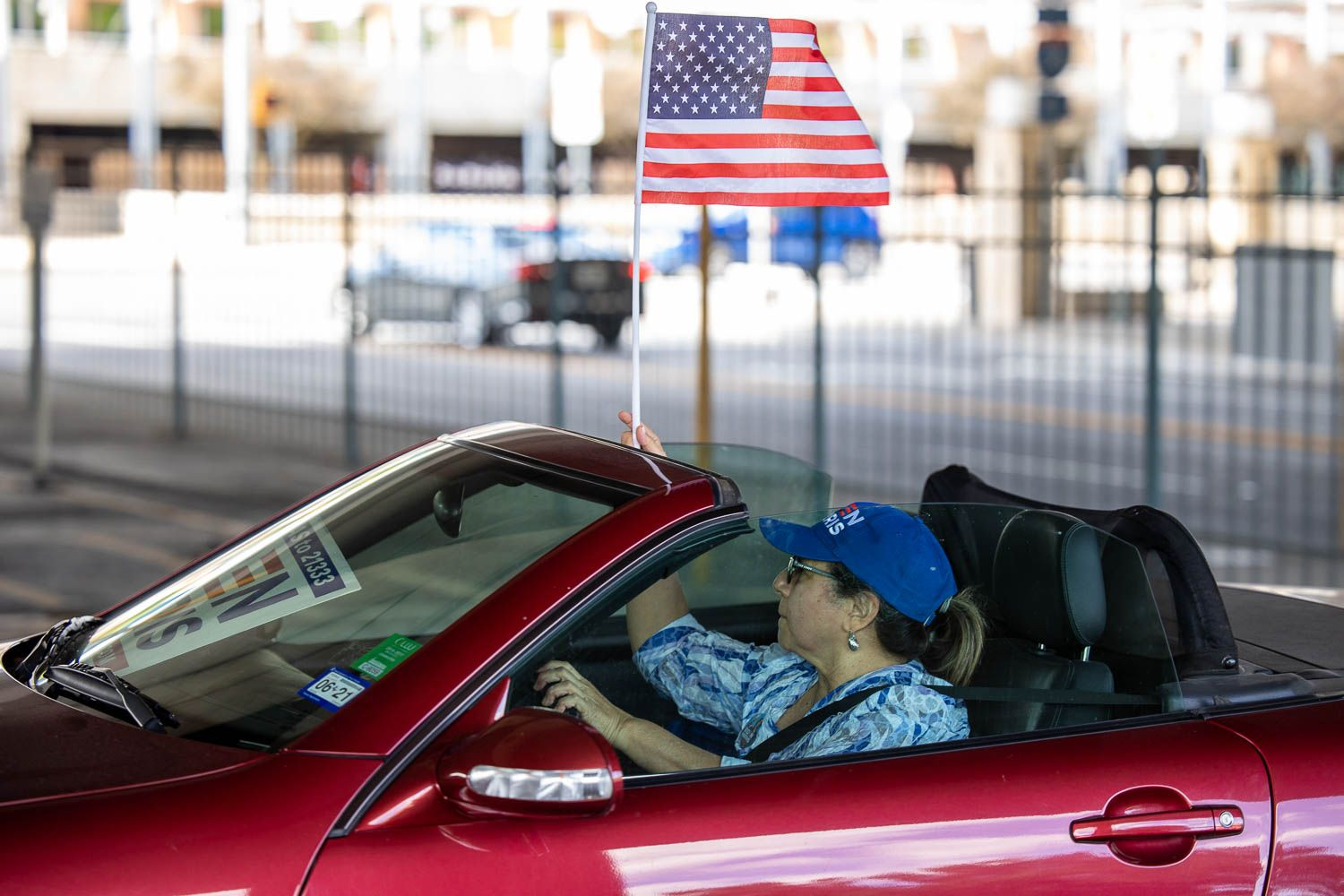 A driver holding up the American flag as  San Antonians caravaned through downtown to celebrate the President-elect Joe Biden and Kamala Harris's win on November 7, 2020. Photo by Stephanie Marquez | Heron contributor