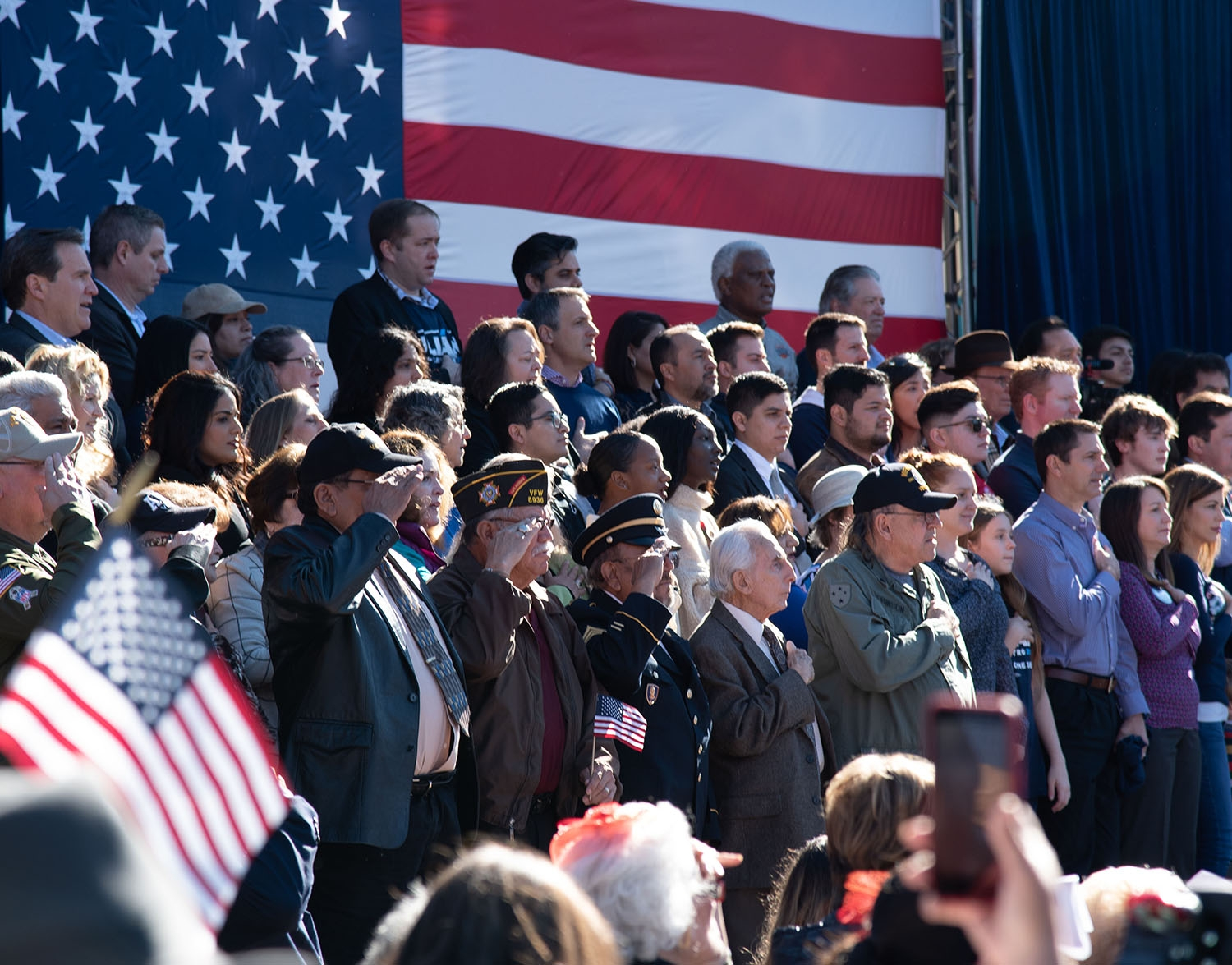 Attendees stand for The Star-Spangled Banner before Julián Castro speaks Jan. 12 at Plaza Guadalupe. Photo: V. Finster | Heron contributor