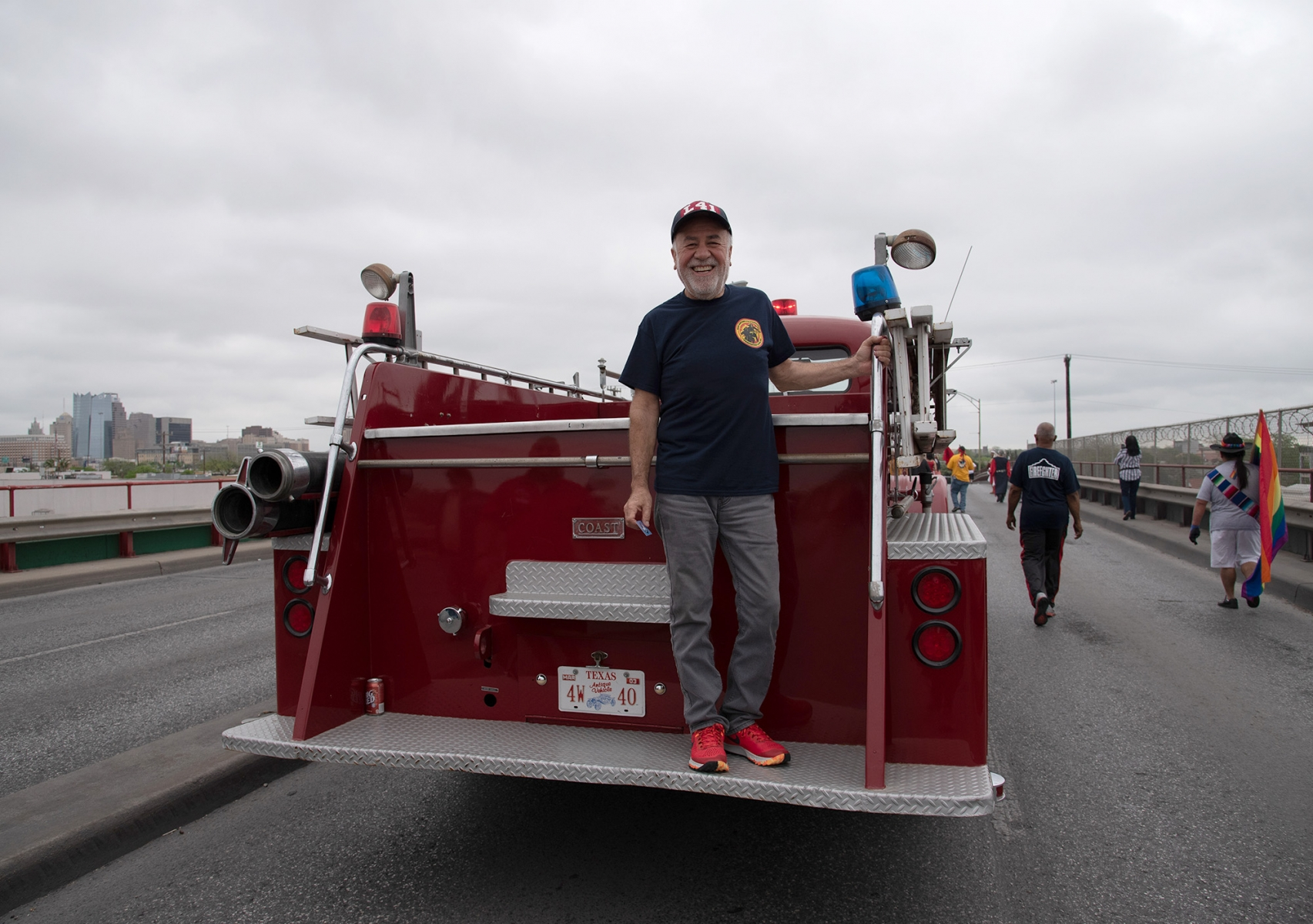 Joel Gonzalez, retired firefighter, stands on the back of an antique firetruck during San Antonio's 23rd annual César E. Chávez March for Justice on Saturday, March 30, on Guadalupe Street. Photo by V. Finster | Heron