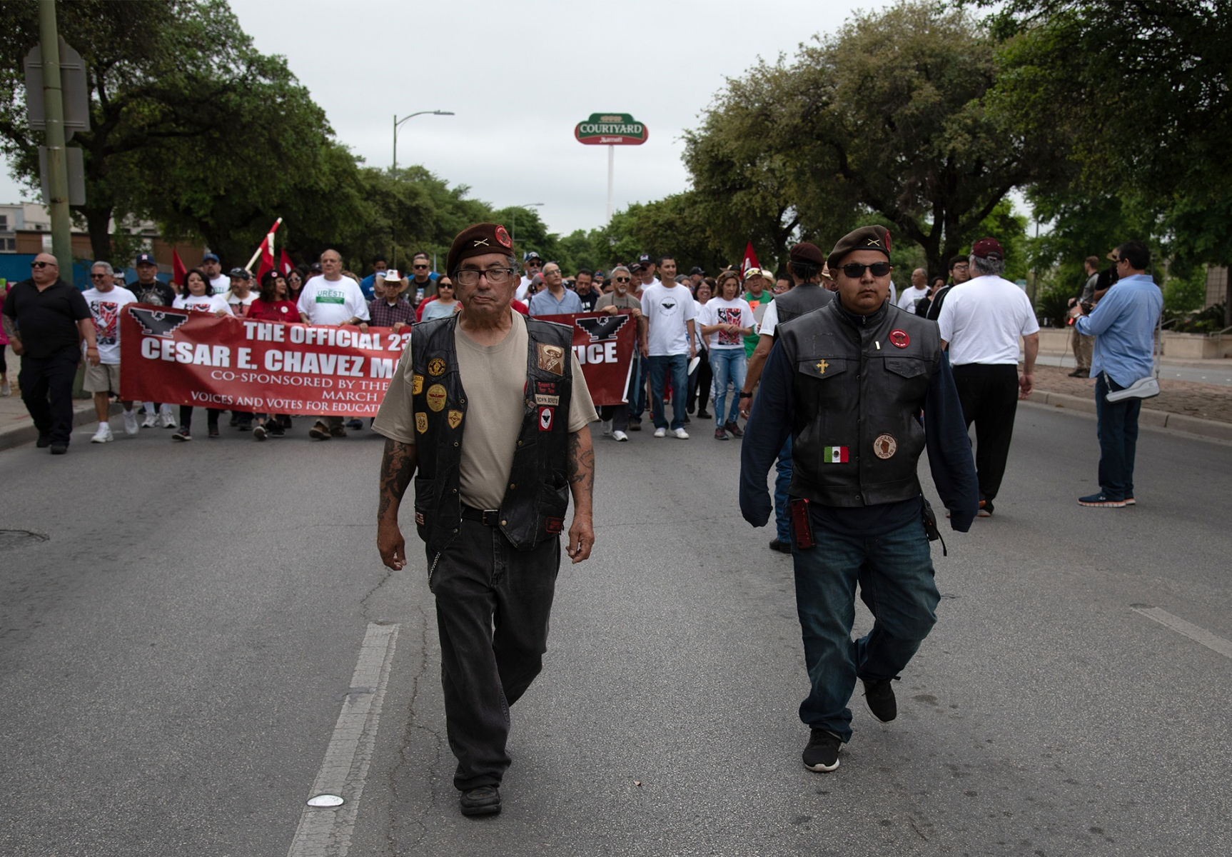 Victor San Miguel (left) and Emmanuel Gomez, members of the Carnalismo Brown Berets of San Antonio, walk in San Antonio's 23rd annual César E. Chávez March for Justice on Saturday, March 30, on South Santa Rosa Avenue. San Miguel has been a member of the San Antonio chapter since the 1960s.  Photo by V. Finster | Heron