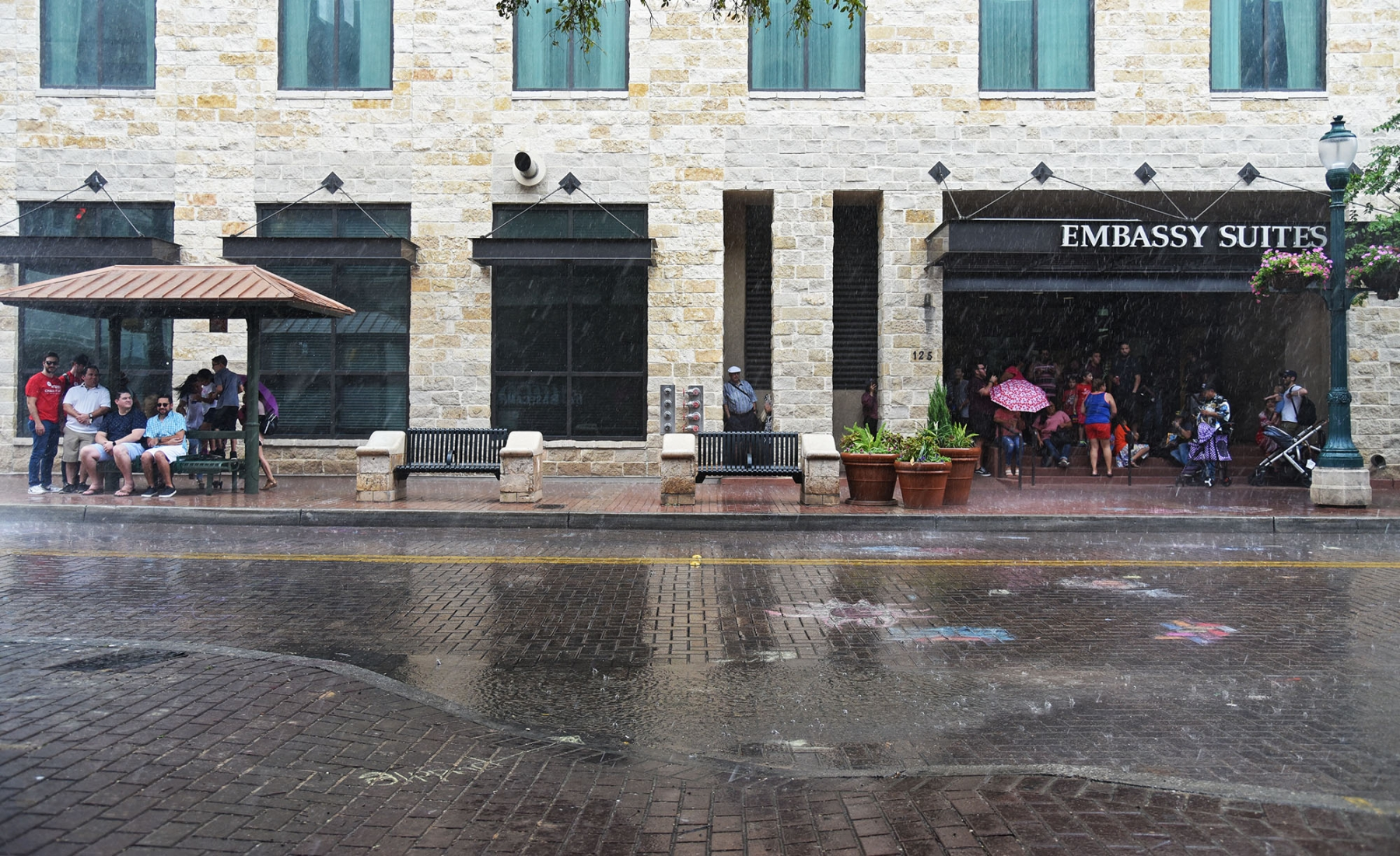 Attendees at the 15th annual Chalk It Up sit at a bus stop and under an Embassy Suites awning during a brief rain shower Oct. 13 in downtown San Antonio.  <em><b>Photo by V. Finster | Heron</b></em>