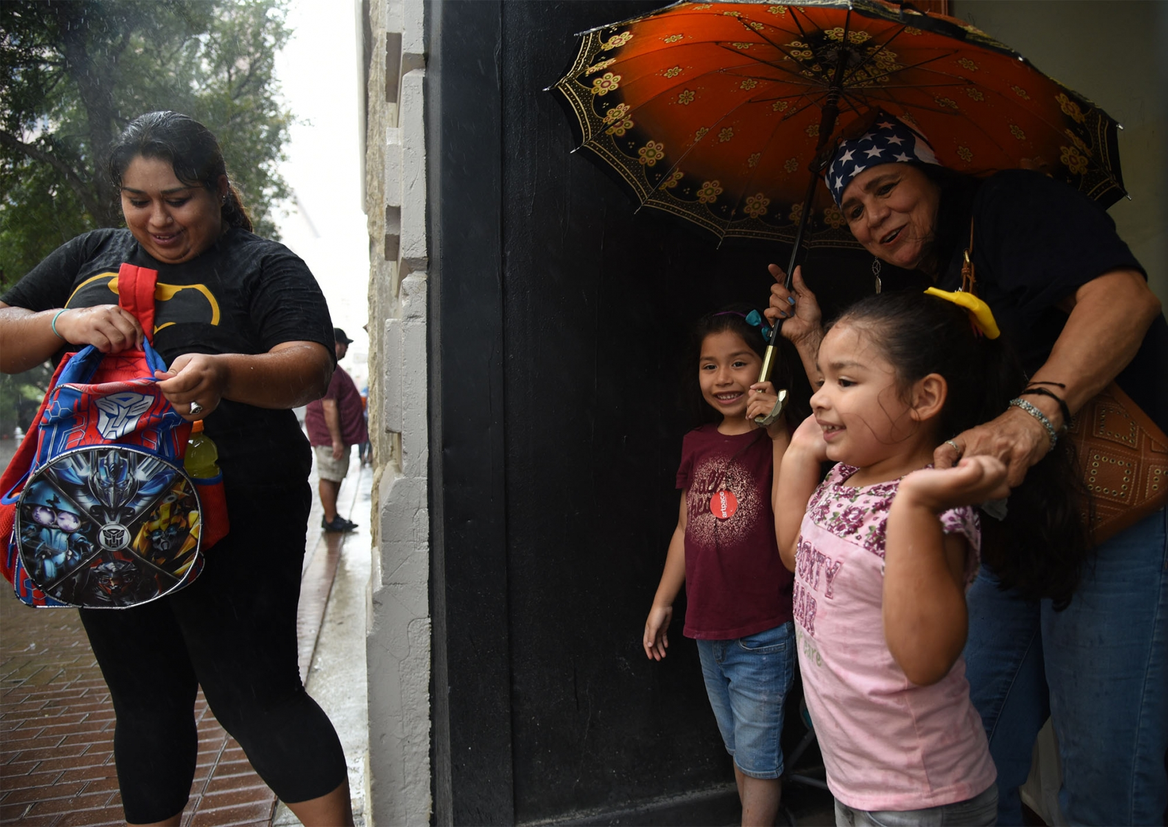 Valerie Gallerdo stands in the rain while her children Adrianna Guitierrez, 5, and Natalie Guitierrez, 4, wait with grandmother Martha Arollo during the 15th annual Chalk It Up event in downtown San Antonio. <em><b>Photo by V. Finster | Heron</b></em>