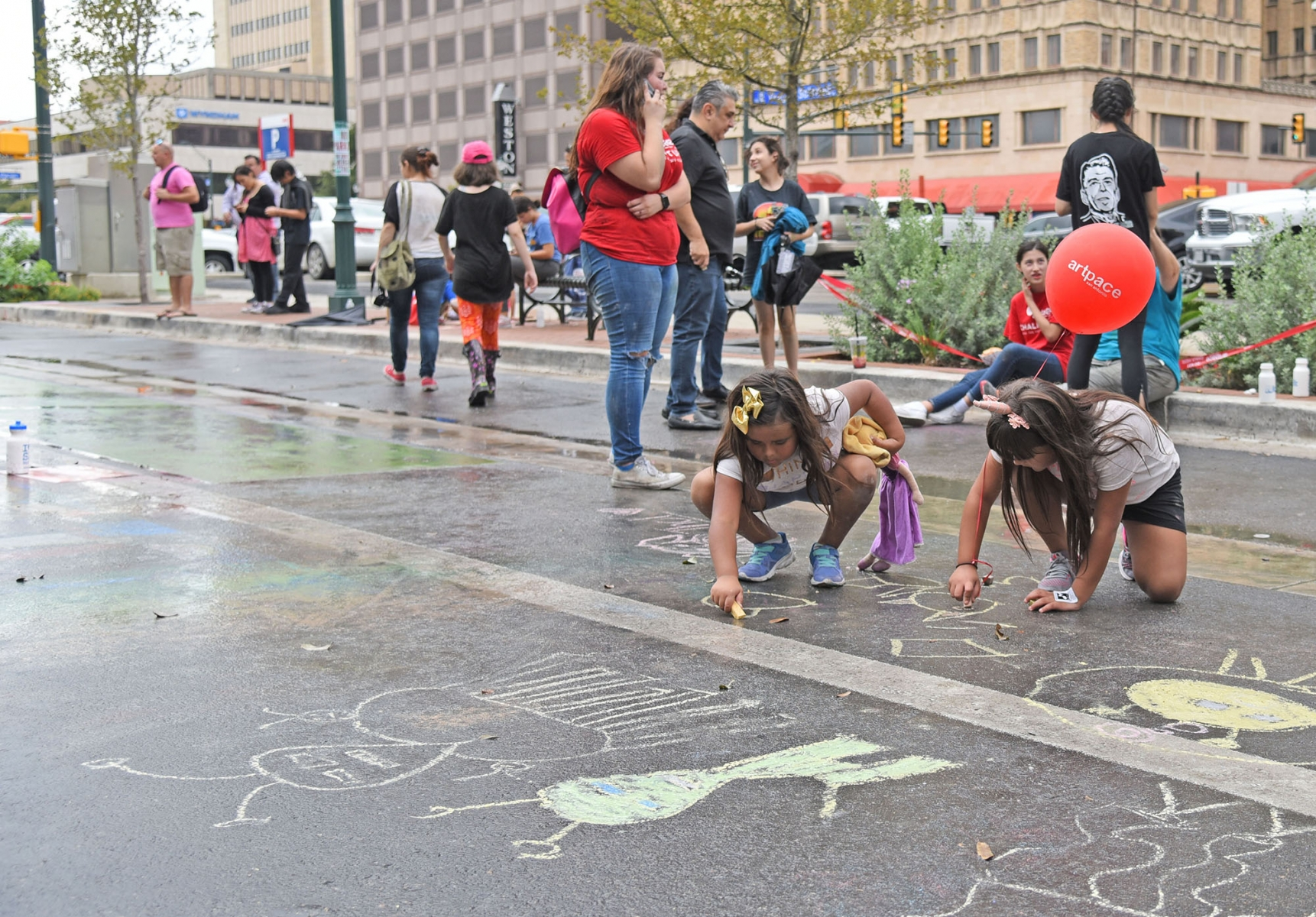 Emily Gonzalez and Jaylinn Urdiales draw with chalk after a brief rain during the 15th annual Chalk It Up in downtown San Antonio.  <em><b>Photo by V. Finster | Heron</b></em>