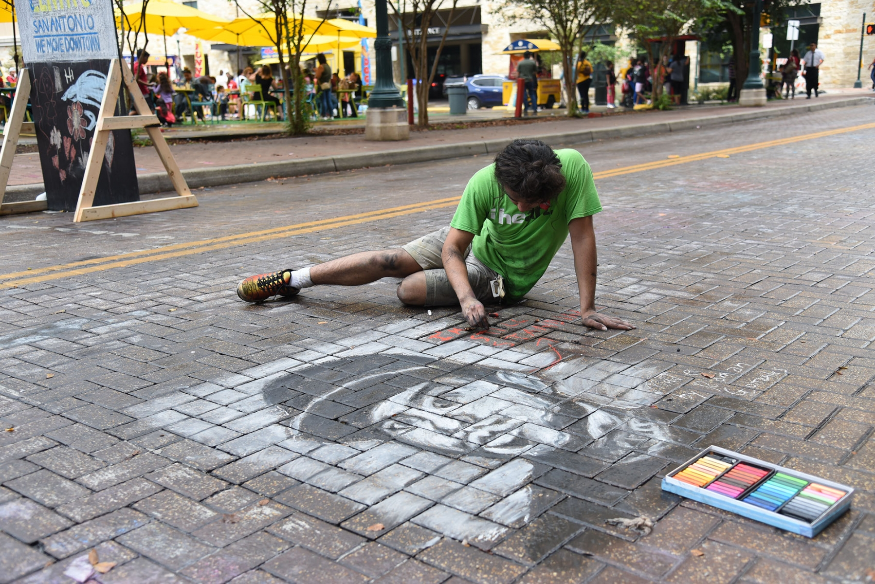 Roman Gonzales, junior at KIPP University Prep draws at the 15th annual Chalk It Up Oct. 13 in downtown San Antonio. <em><b>Photo by V. Finster | Heron</b></em>