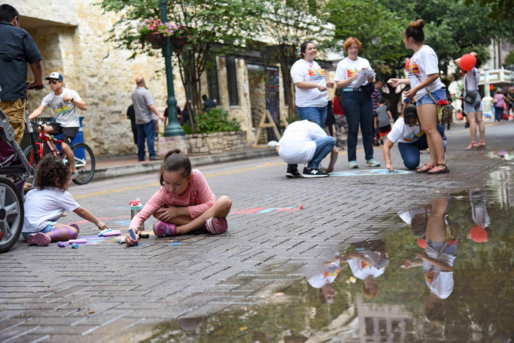 Sisters Reagan and Andrea Morin draw at the 15th annual Chalk It Up after a breif rain Oct. 13 in Downtown San Antonio.  <em><b>Photo by V. Finster | Heron</b></em>