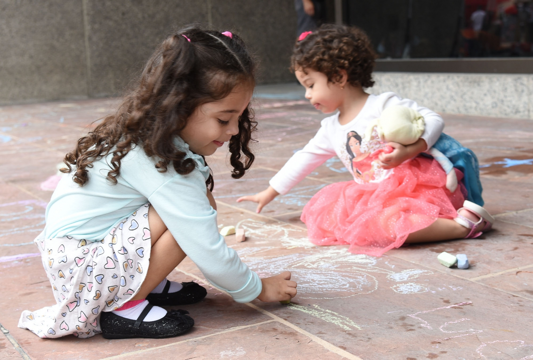 "Lucia and Lilia Villanueva draw an ""ocean"" scene during the 15th annual Chalk It Up Oct. 13 in downtown San Antonio. <em><b>Photo by V. Finster 