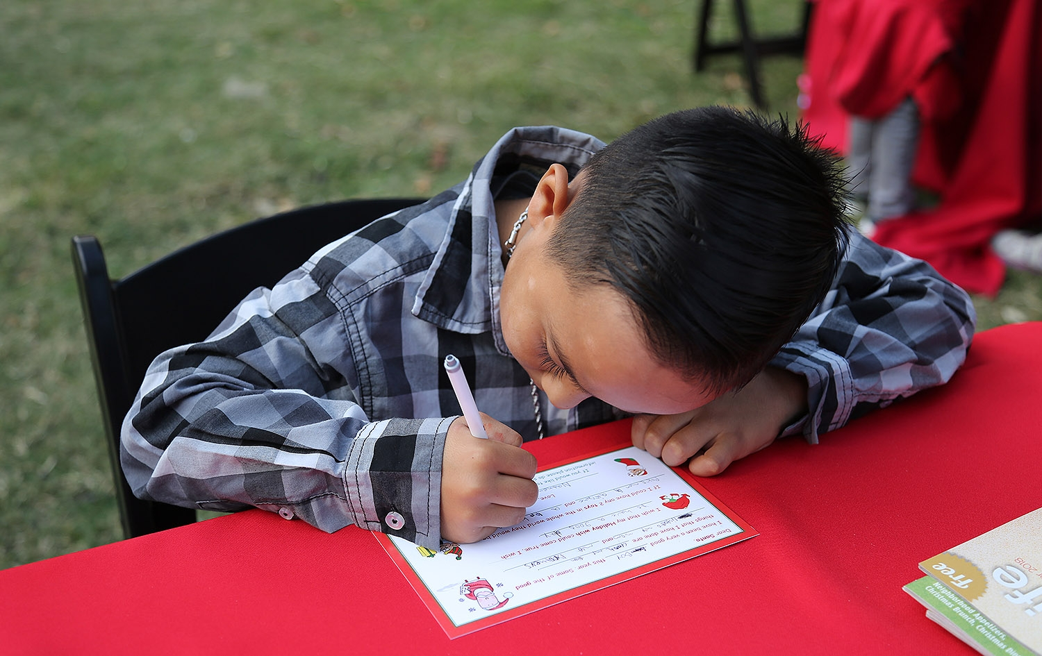 Nathen Escobedo, 8, writes a letter to Santa during the H-E-B Christmas Tree Lighting Celebration Friday at Travis Park. <em><b>Photo by Ben Olivo | Heron</b></em>