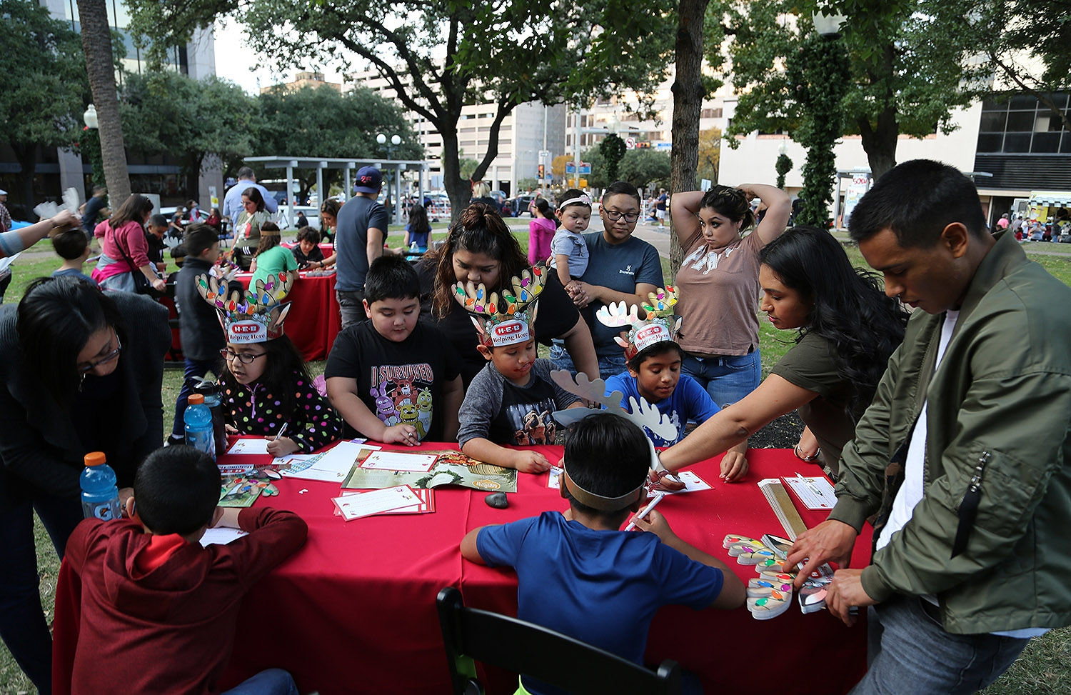 Members of the Salinas and Garza families (unrelated) write letters to Santa Claus during the H-E-B Christmas Tree Lighting Celebration Friday at Travis Park. <em><b>Photo by Ben Olivo | Heron</b></em>