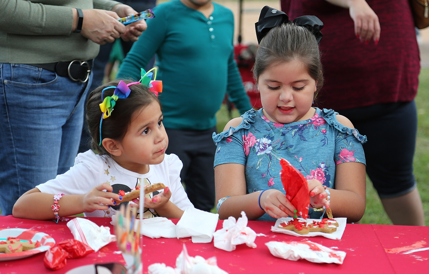 Guinevere (left) and Camilla Adams decorate (and eat) cookies during the H-E-B Christmas Tree Lighting Celebration Friday at Travis Park. <em><b>Photo by Ben Olivo | Heron</b></em>