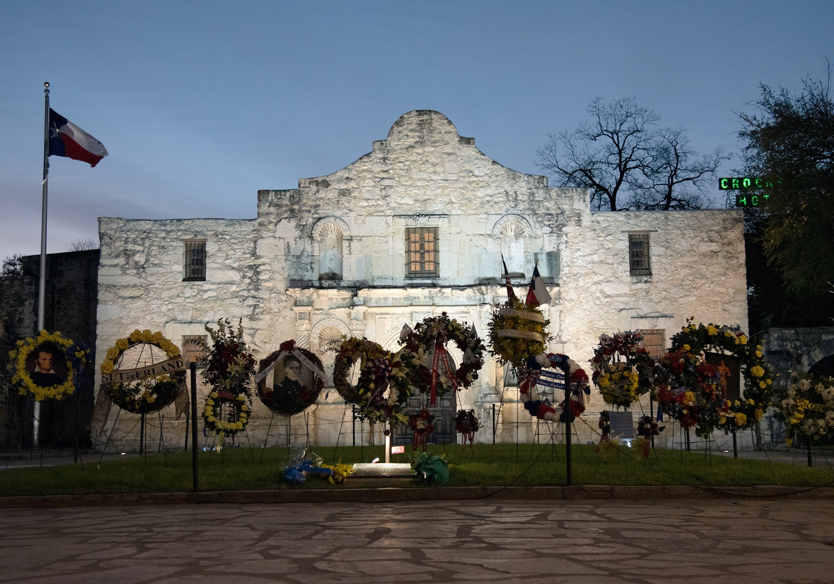 Flowers and wreaths are placed in front of the Alamo following the Dawn at the Alamo ceremony March 6, 2019, at Alamo Plaza.