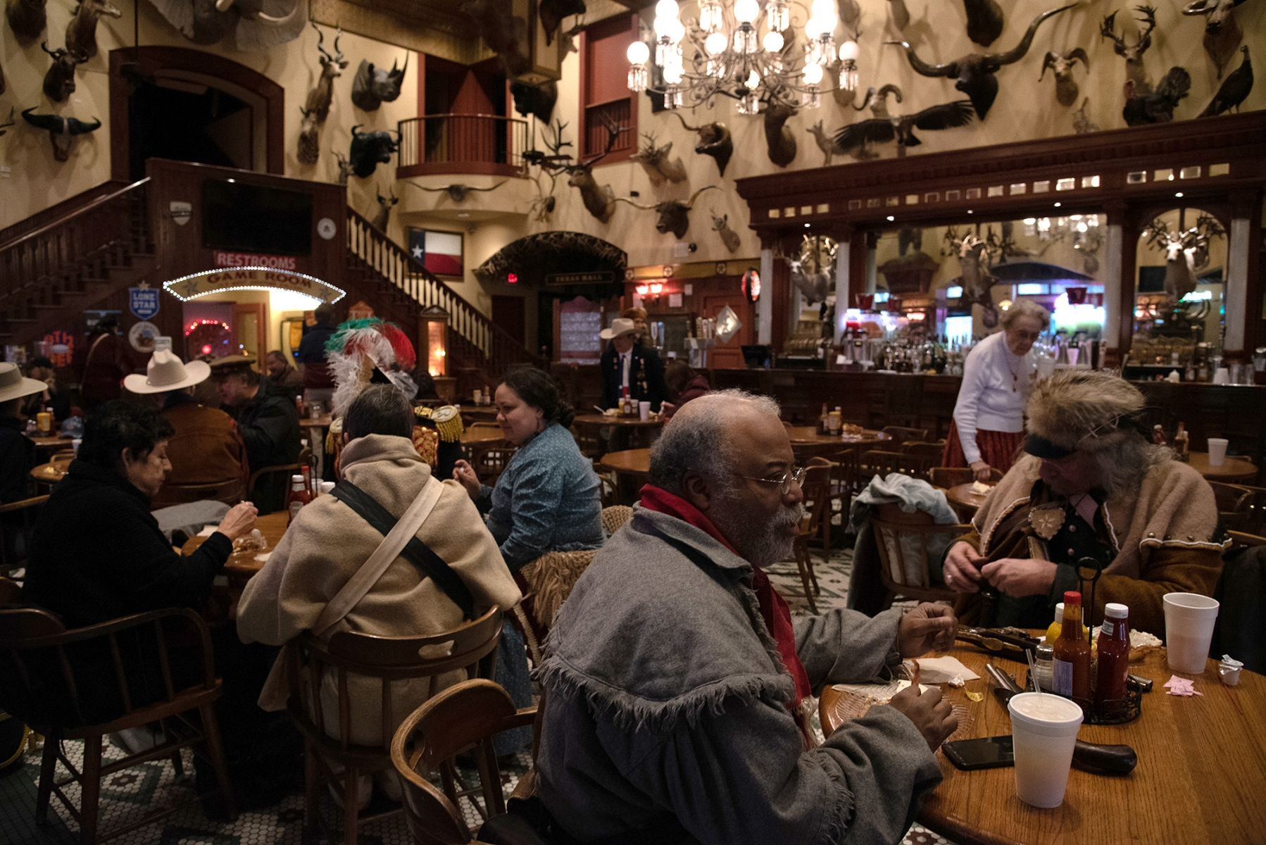 Some individuals who participated in the Dawn at the Alamo ceremony eat breakfast after the event March 6, 2019, at the Buckhorn Saloon.