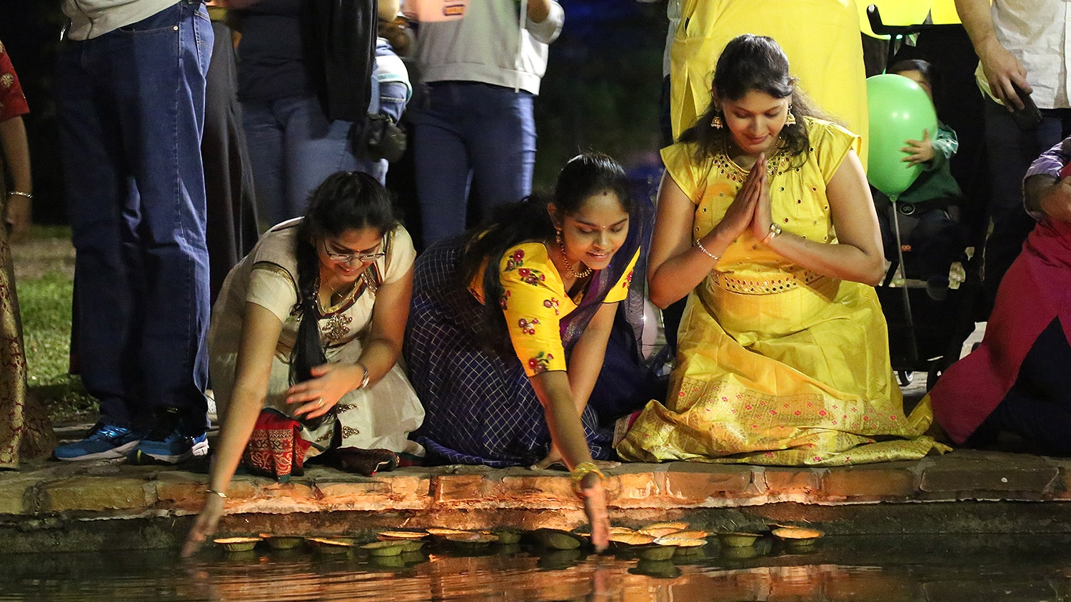 Indhu Masanam (from left), Vyshnavi Nelaturi and Madhuri Chundu release diyas during the 10th annual Diwali festival at Hemisfair. <em><b>Photo by Ben Olivo | Heron</b></em>