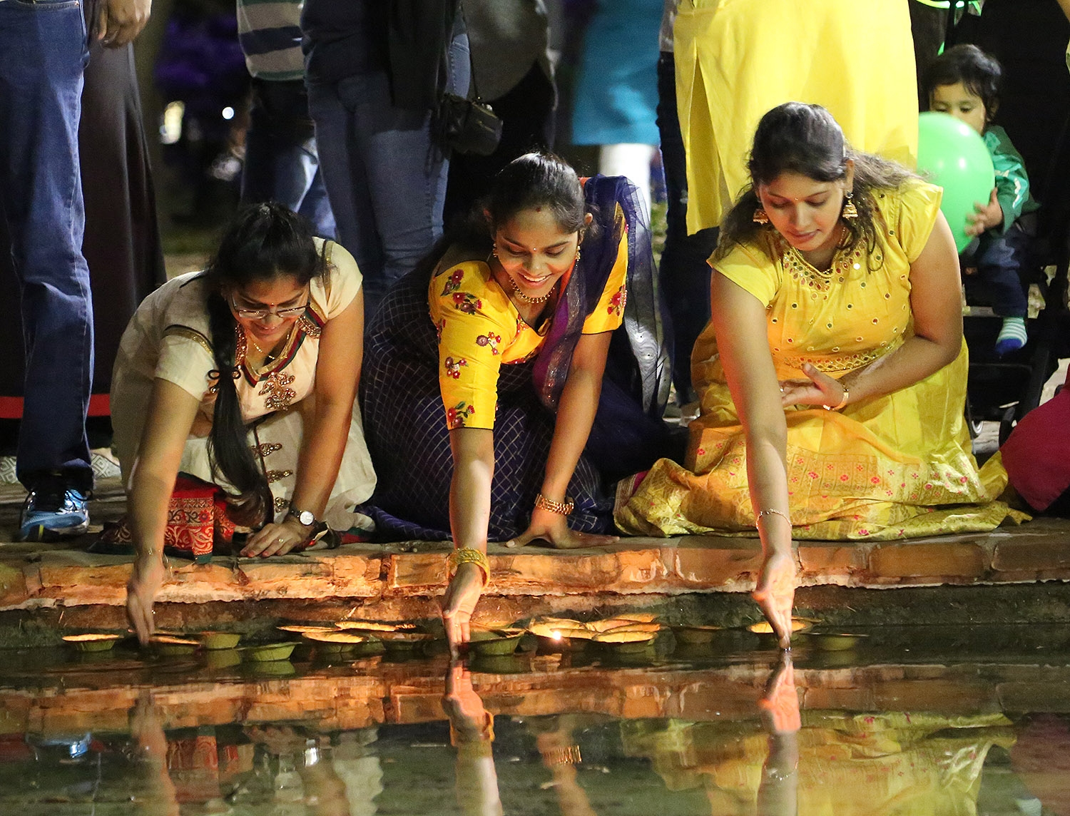 Indhu Masanam (from left), Vyshnavi Nelaturi and Madhuri Chundu release diyas during the 10th annual Diwali festival Nov. 3 at Hemisfair. <em><b>Photo by Ben Olivo | Heron</b></em>
