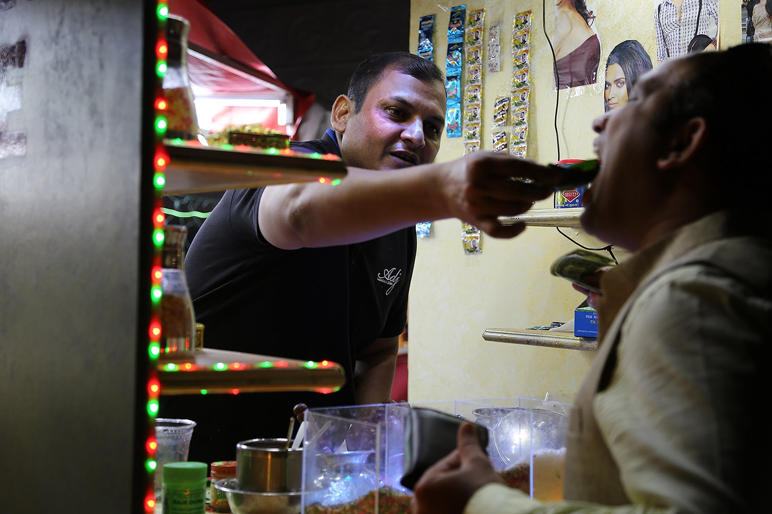 Kashif Ahmed feeds a customer at the Mustafa Paan House. <em><b>Photo by Ben Olivo | Heron</b></em>