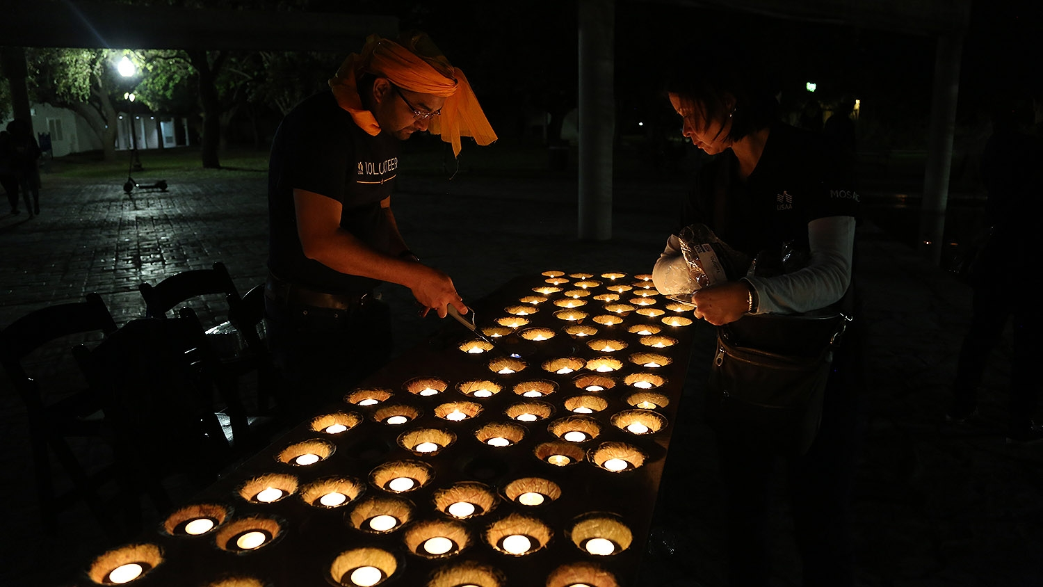USAA volunteers Pavan Gosai (left) and Kim Nguyen light diyas at the 10th annual Diwali festival at Hemisfair. <em><b>Photo by Ben Olivo | Heron</b></em>