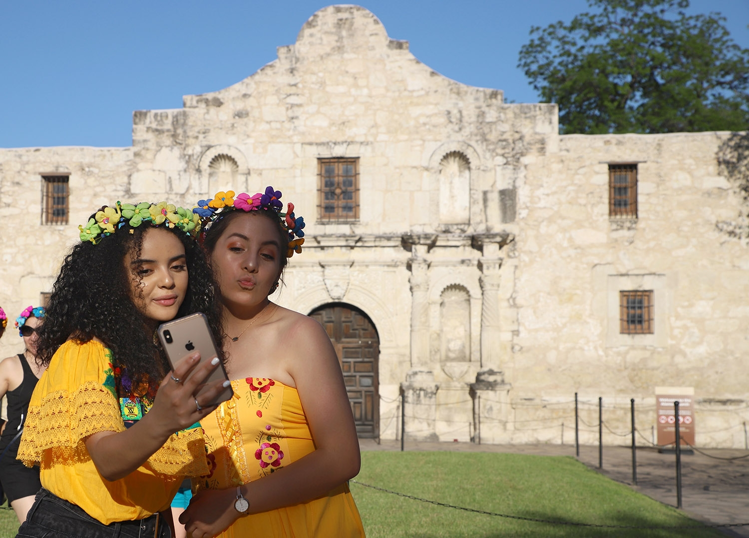 Two young girls take a selfie in front of the Alamo while waiting for the Flambeau Parade to start on Saturday. <em>Photo by Brianna Rodrigue | Heron contributor</em>