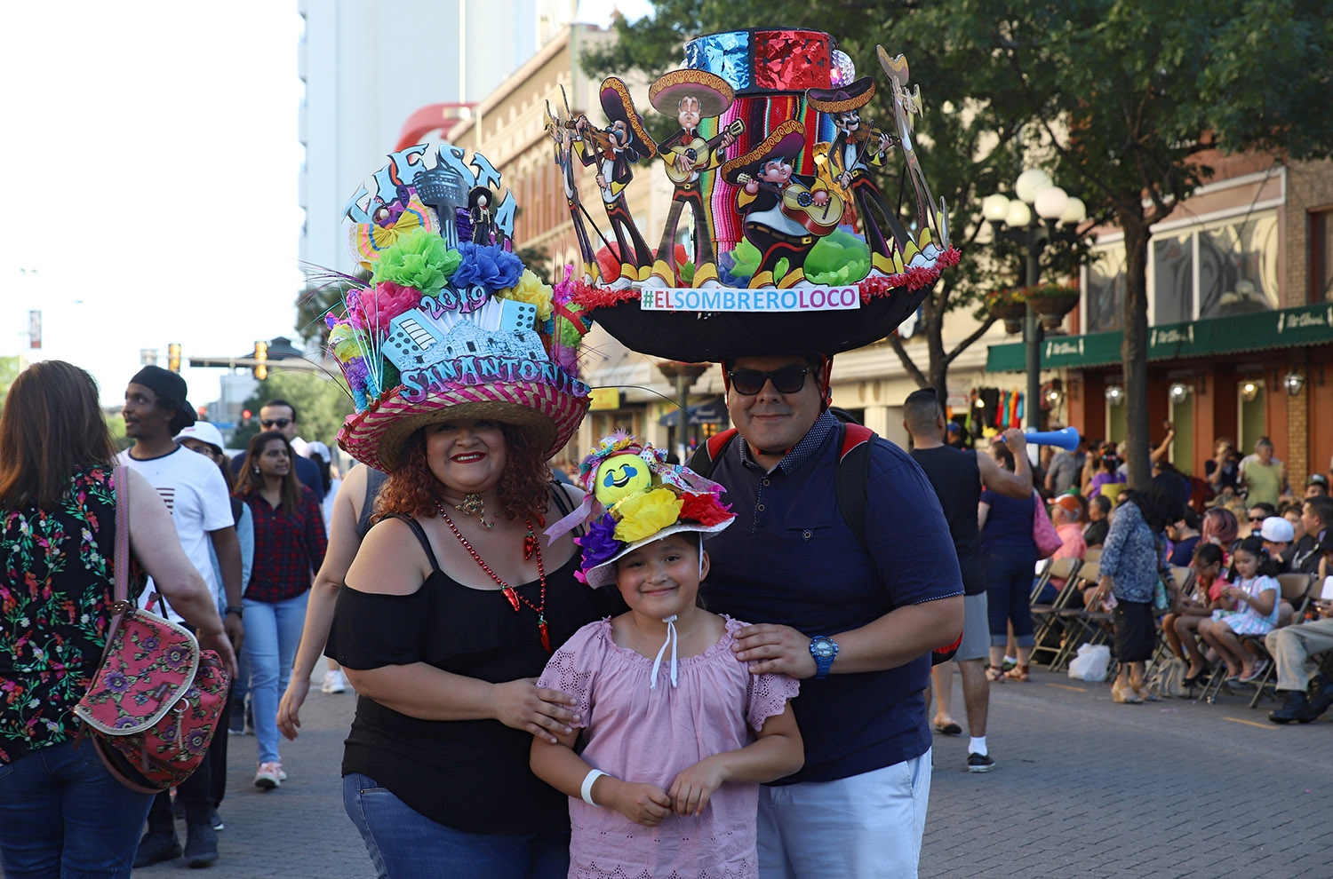 Mary Martinez, 36; Avinna Martinez, 7; and Candelario Gomez, 35, show off their Fiesta hats at the Flambeau Parade on Saturday. Gomez said his hat weighs 15 pounds because it holds a disco ball and two speakers. <em>Photo by Brianna Rodrigue | Heron contributor</em>