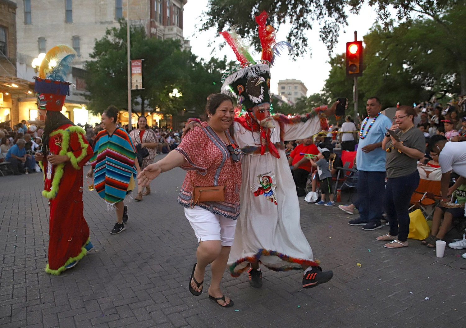 Annette Rodriguez, 61, dances with a member from the Comparsa de Chinelos Herencia Morelense en Houston during the Flambeau Parade on Saturday. <em>Photo by Brianna Rodrigue | Heron contributor</em>
