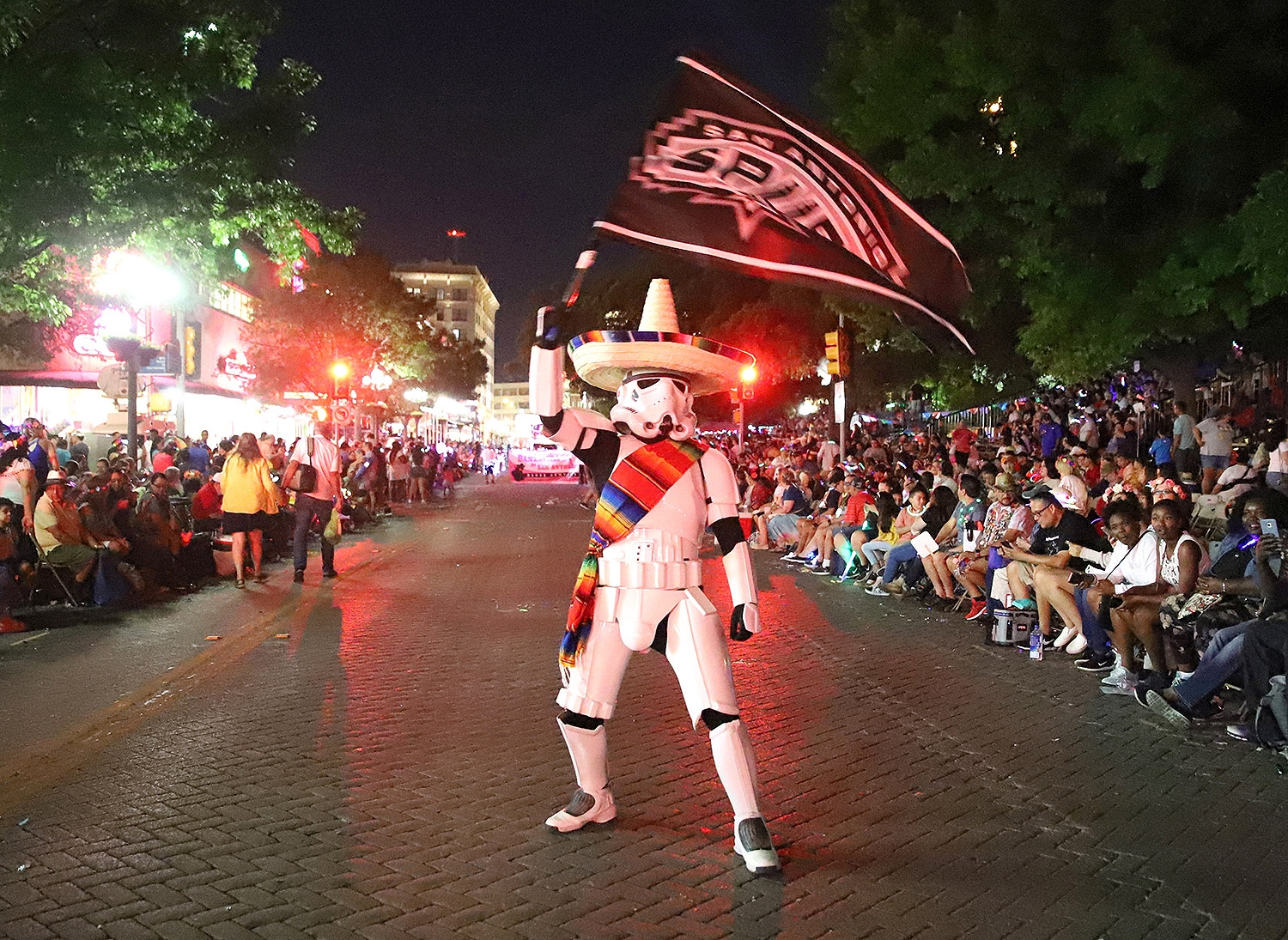 A stormtrooper sways a Spurs flag in front of a crowd on Alamo Plaza during the Flambeau Parade. <em>Photo by Brianna Rodrigue | Heron contributor</em>