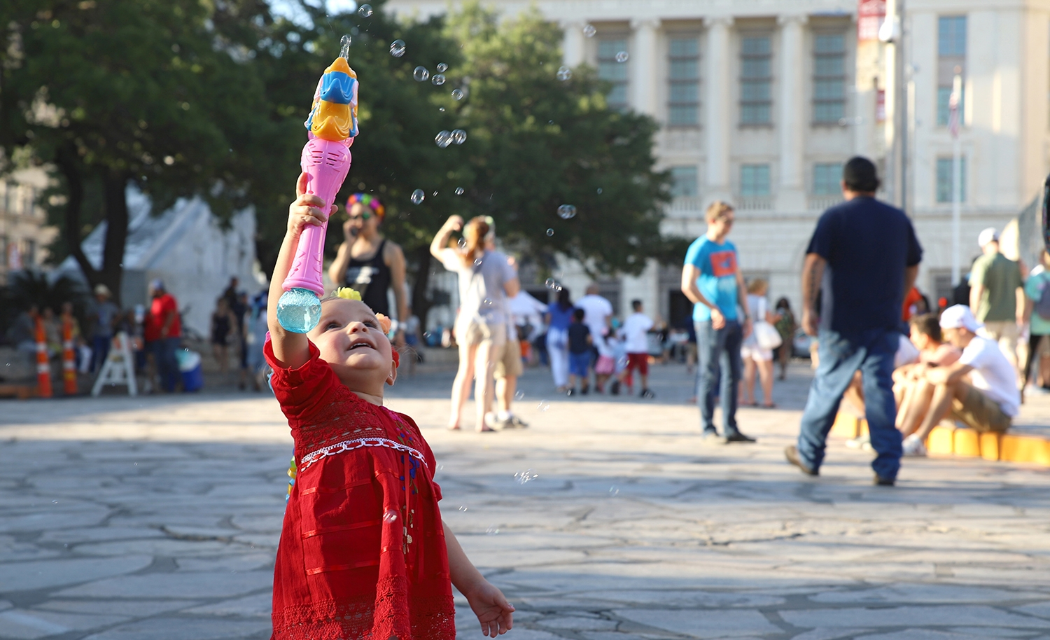 Ellie Valdez, 2, shoots bubbles in the air in front of the Alamo before the start of the Flambeau Parade on Saturday. <em>Photo by Brianna Rodrigue | Heron contributor</em>