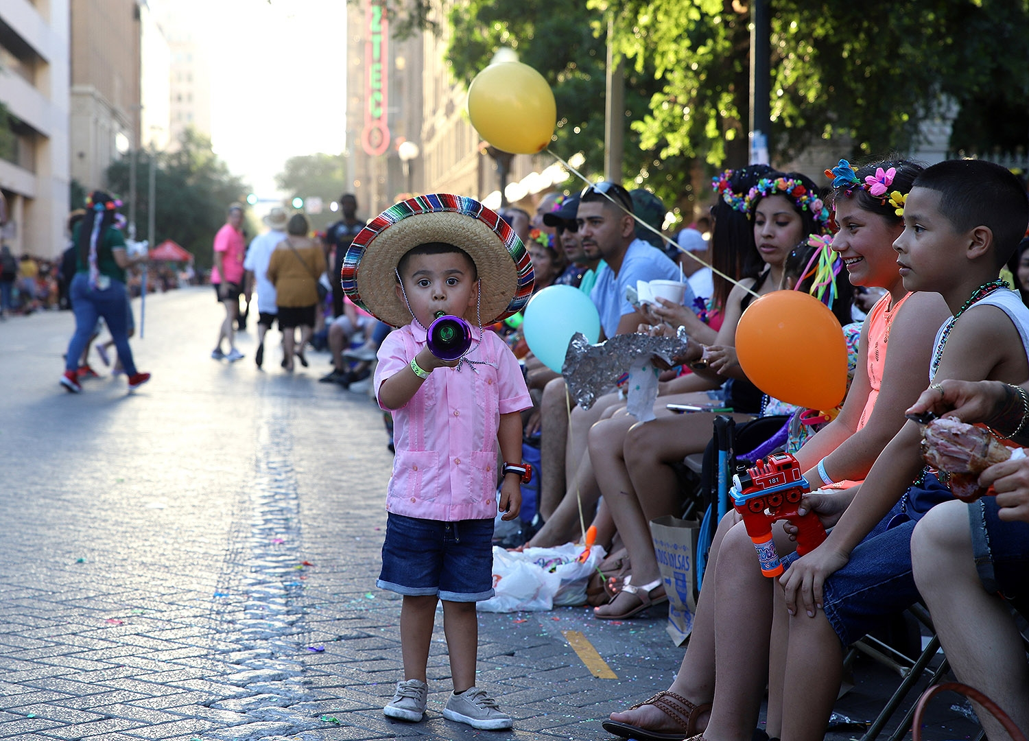 Jeremie Montes, 3, blows a horn before the start of the Flambeau Parade on Saturday. This is Montes and his family third year attending the parade. <em>Photo by Brianna Rodrigue | Heron contributor</em>
