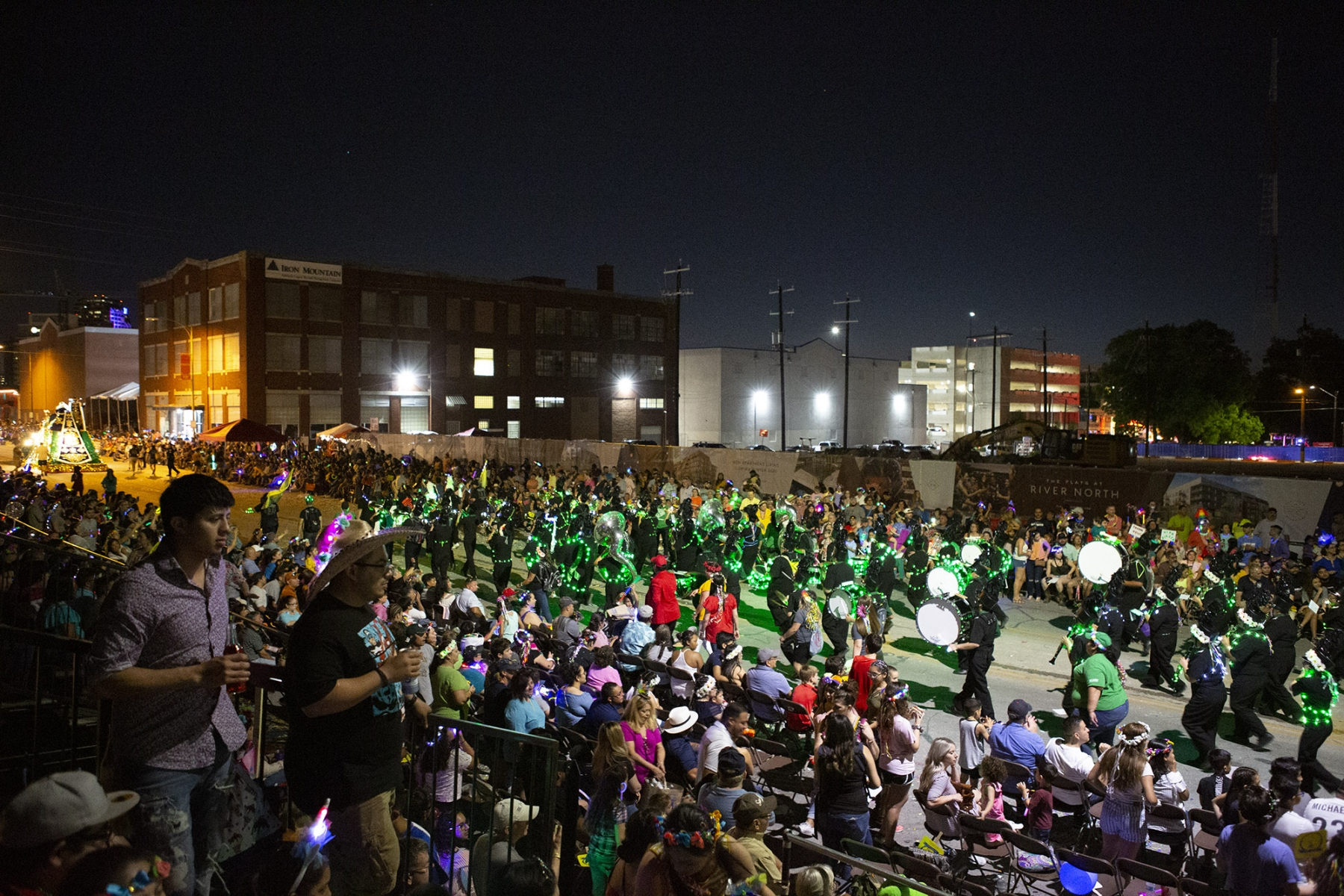 The crowd watches as a band goes by during the Fiesta Flambeau Parade on Saturday, April 27. <em>Photo by Kara Hawley | Heron contributor</em>