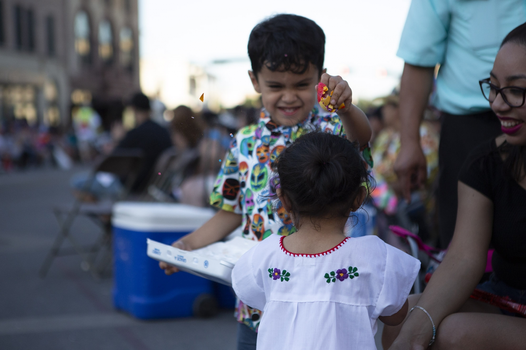 Isaiah Castaneda, 4, showers his sister in confetti while waiting for the Fiesta Flambeau Parade Saturday, April 27. <em>Photo by Kara Hawley | Heron contributor</em>