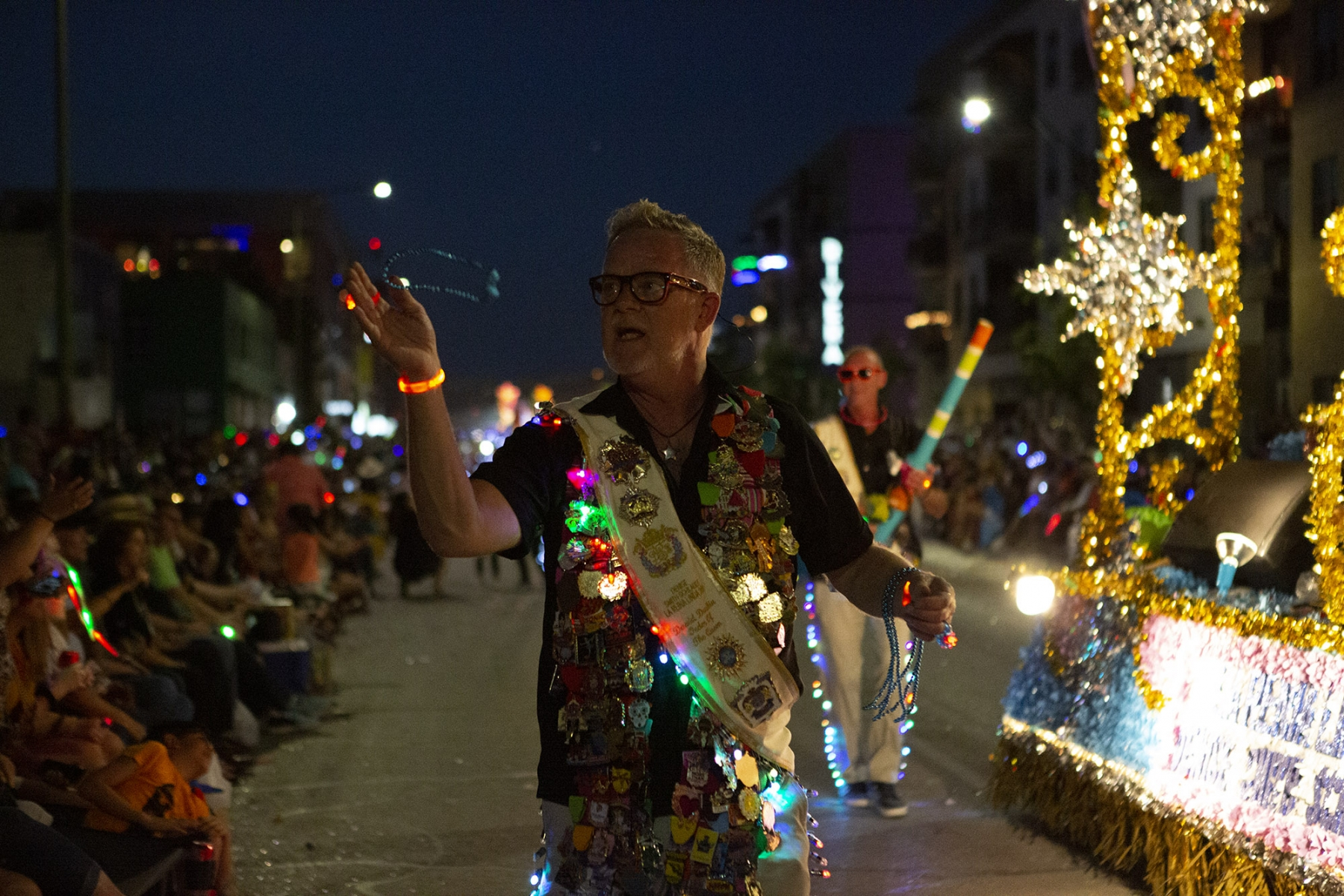 A man throws beaded necklaces into the corwd at the Fiesta Flambeau Parade on Saturday, April 27. <em>Photo by Kara Hawley | Heron contributor</em>