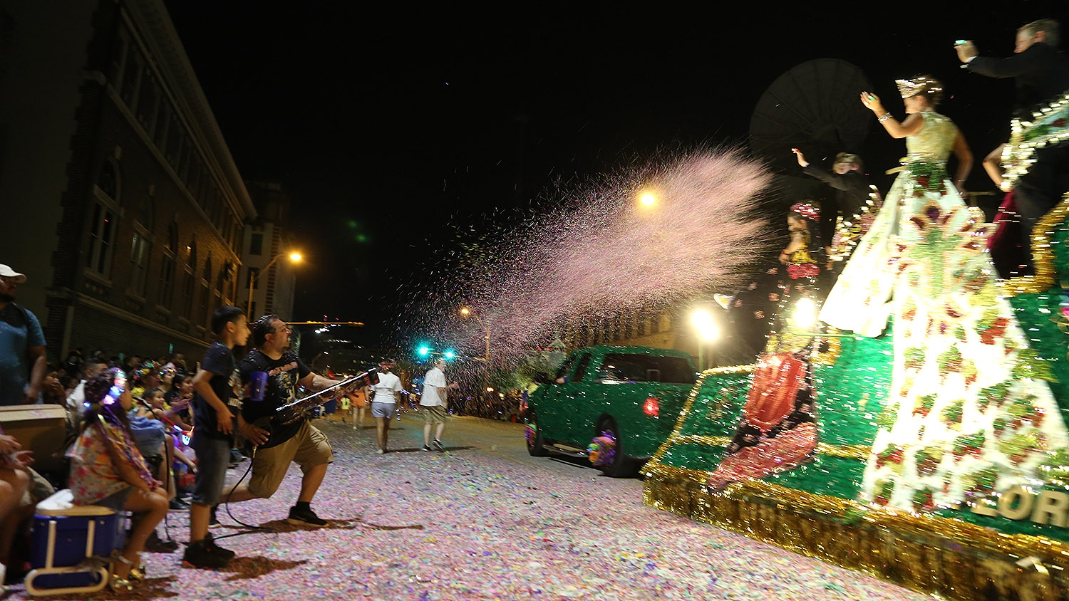 Alex De Leon fires a confetti cannon at the Floresville Peanut Festival float during the Fiesta Flambeau Parade on Saturday night. <em>Photo by Ben Olivo | Heron</em>