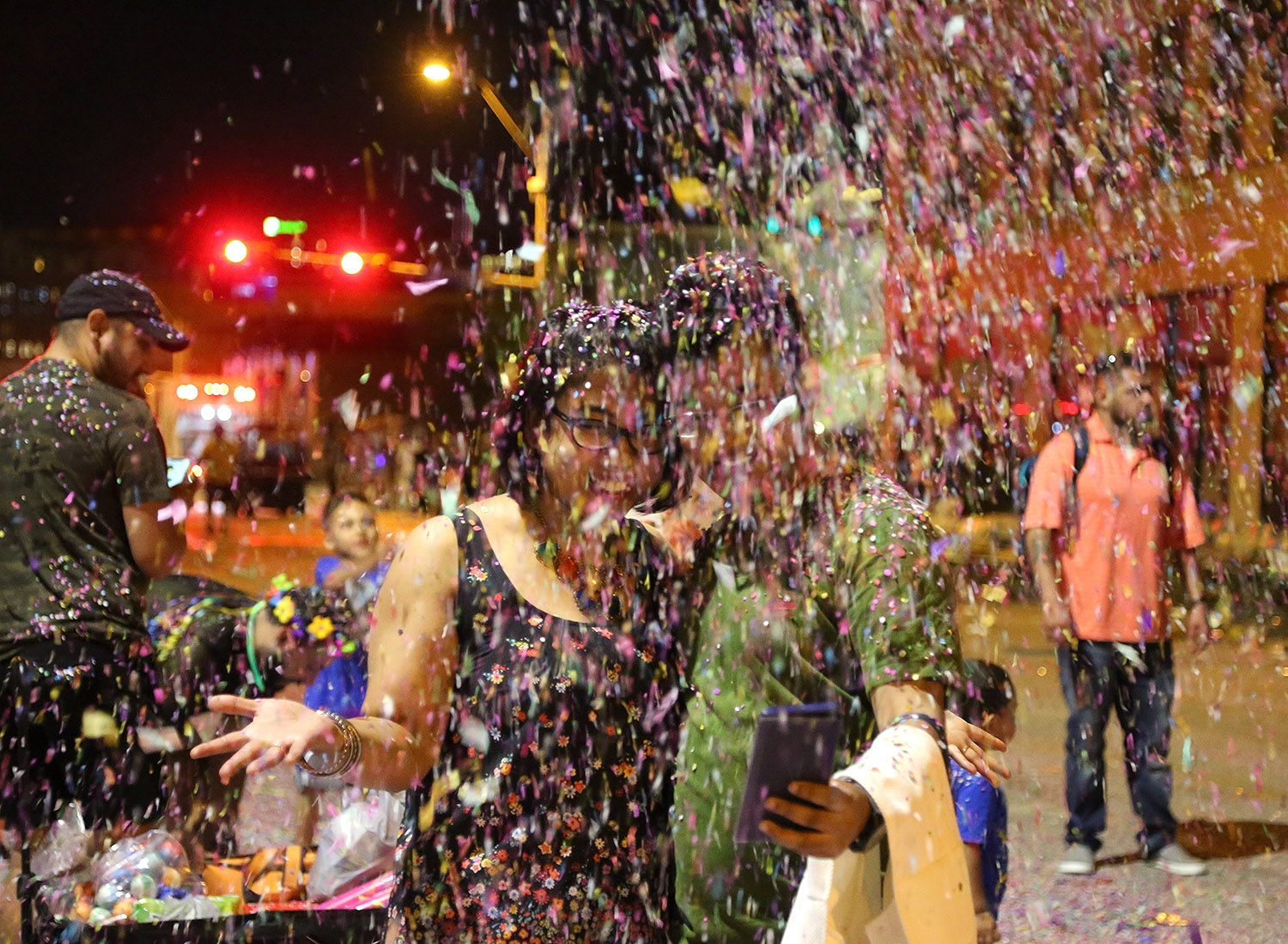 Keka Nandi (left) and Sumit Mitra take a confetti selfie after the Fiesta Flambeau parade on Saturday. <em>Photo by Ben Olivo | Heron</em>