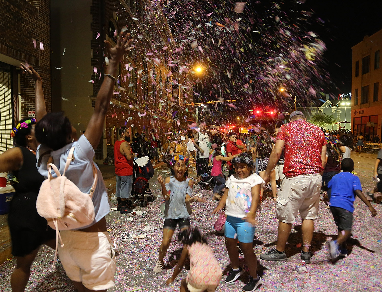 Members of the Giles family have a confetti party after the Fiesta Flambeau Parade on Saturday.  <em>Photo by Ben Olivo | Heron</em>
