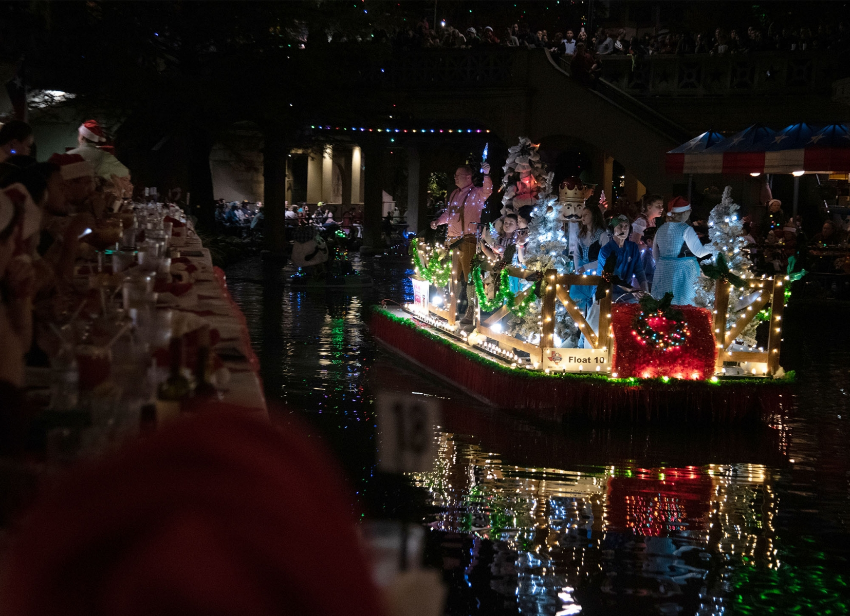 People dine on the River Walk during the annual Ford Holiday River Parade on Friday night. <em><b>Photo by V. Finster | Heron</b></em>
