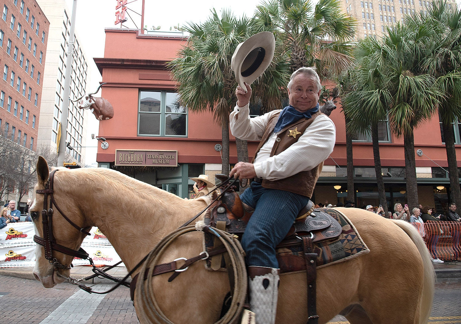 Billy Harris waves his hat to the crowd during the Western Heritage Parade and Cattle Drive Feb. 2 on Houston Street. <em><b>V. Finster | Heron</b></em>