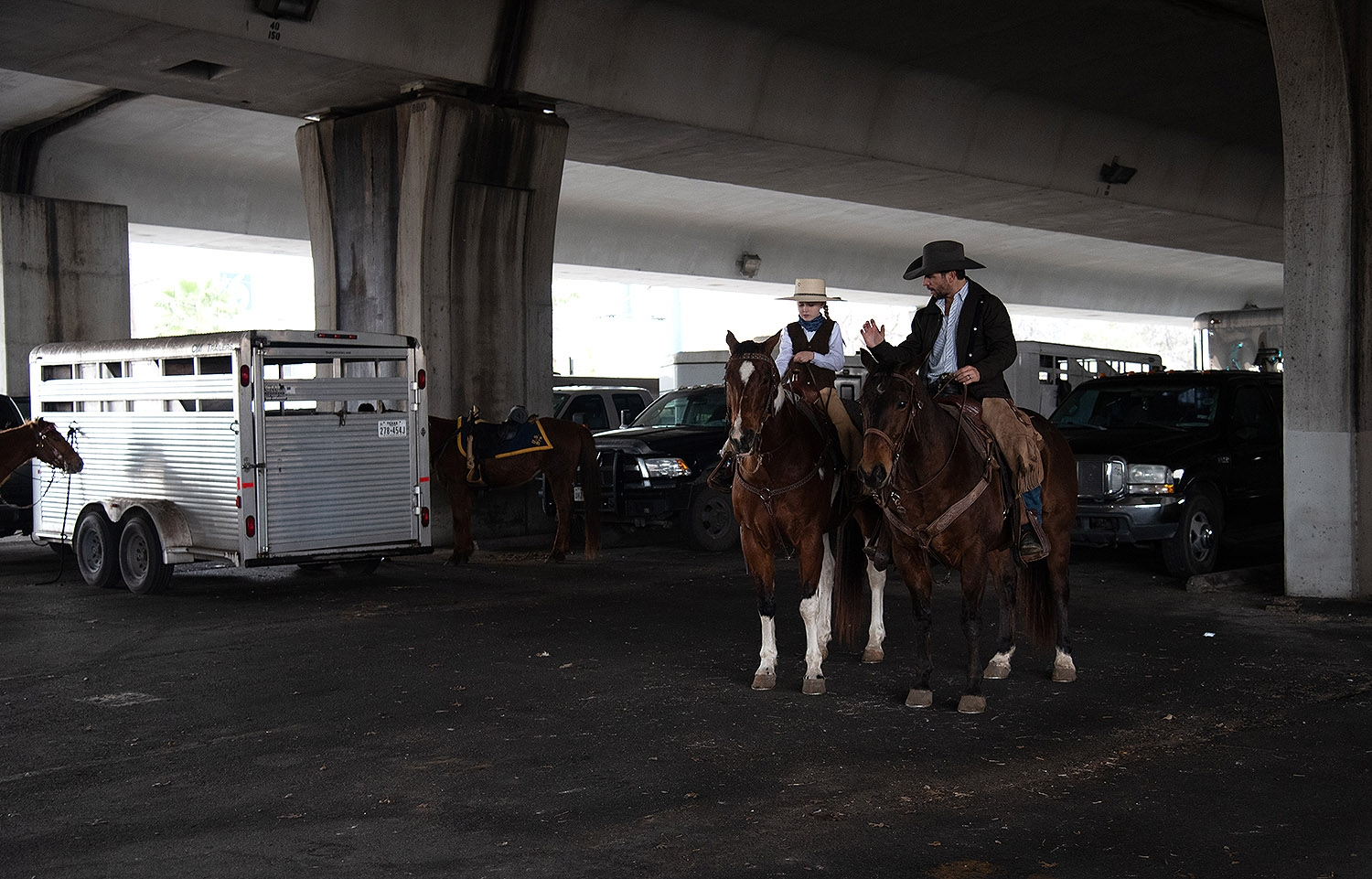 Father Joey Austin speaks to daughter KK Alarid, 8, before the Western Heritage Parade and Cattle Drive Feb. 2 under I-35 at Houston St. <em><b>Photo by V. Finster | Heron</b></em>