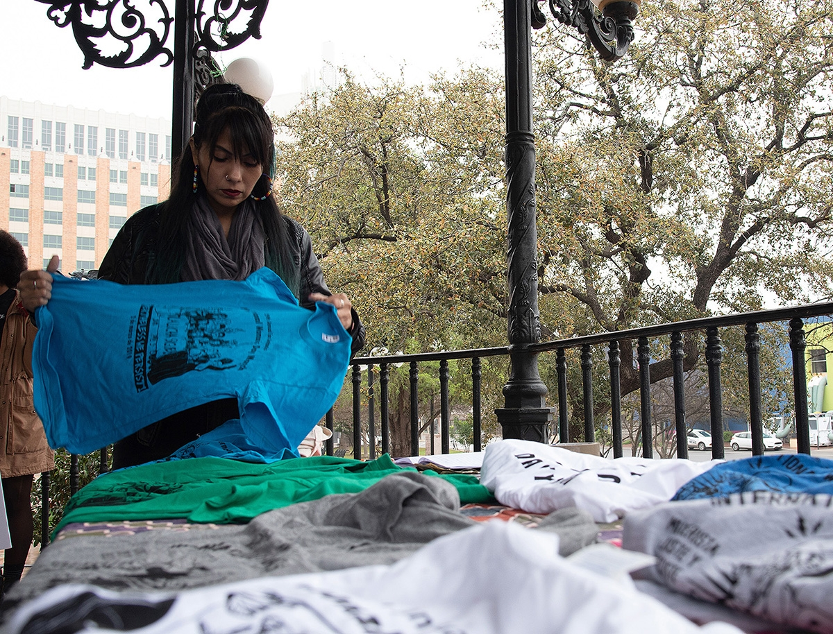 An attendee holds up a shirt for sale before the 29th annual San Antonio International Women's Day March at Milam Park on Saturday, March 2. <b><em>Photo by V. Finster | Heron</em></b>
