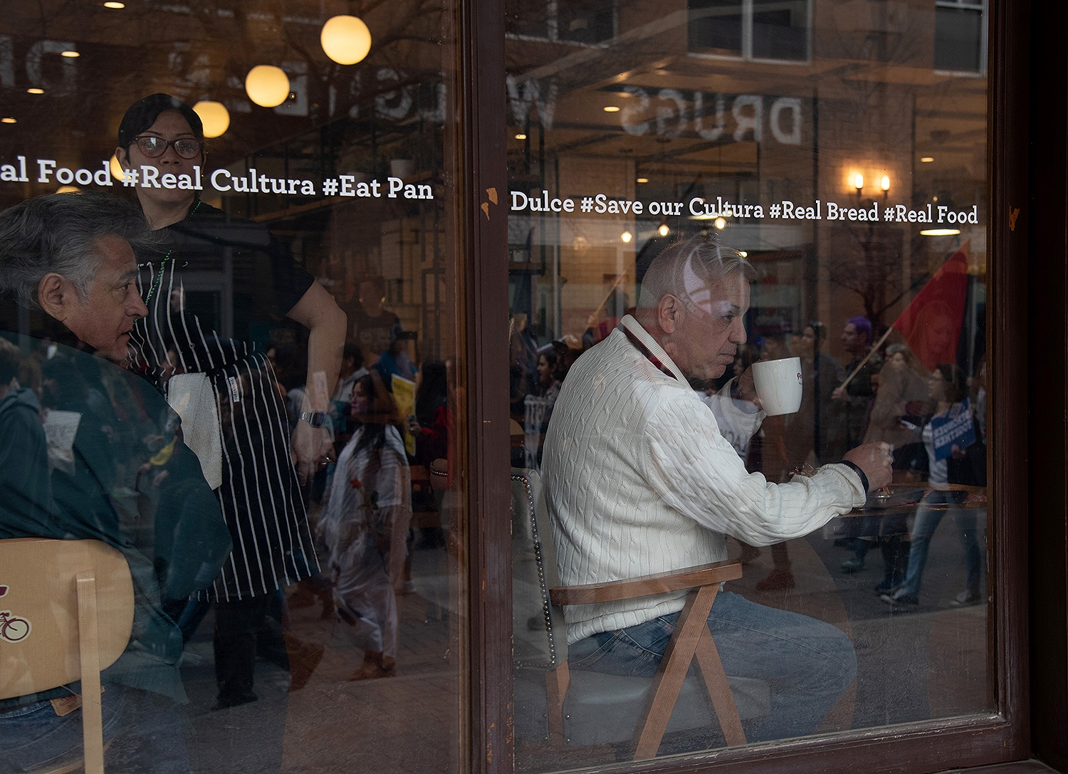 Customers at La Panderia watch participants during the 29th annual San Antonio International Women's Day March on Houston Street on Saturday, March 2 <b><em>Photo by V. Finster | Heron</em></b>