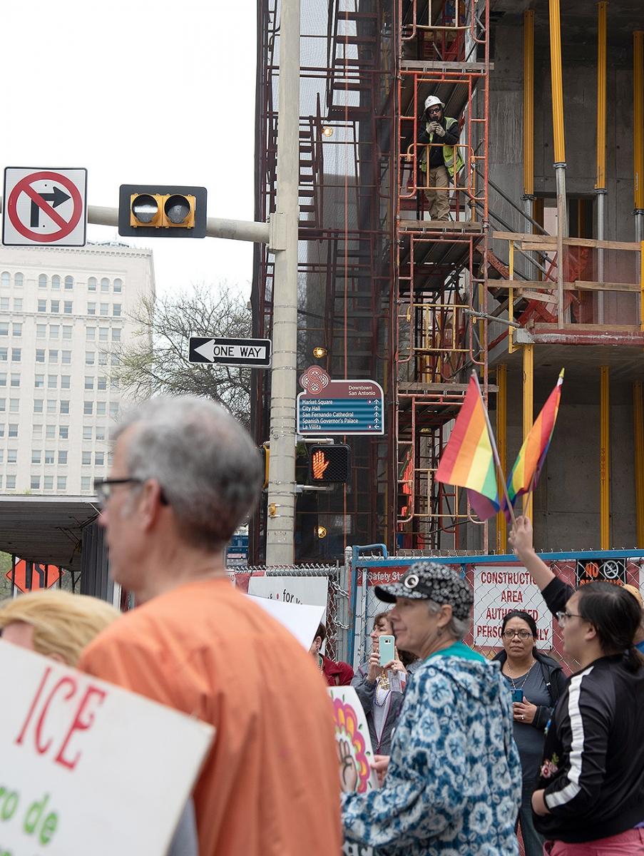 A construction worker watches participants from scaffolding during the 29th annual San Antonio International Women's Day March in downtown San Antonio on Saturday, March 2. <b><em>Photo by V. Finster | Heron</em></b>